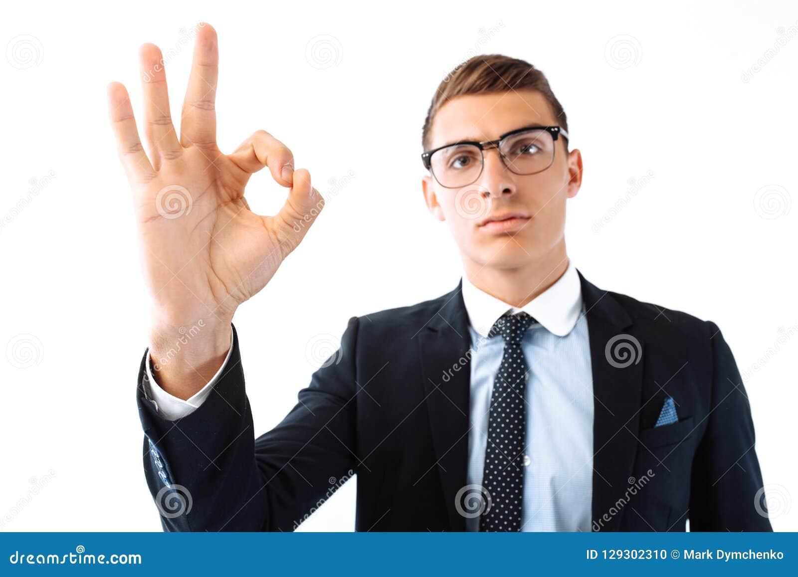 Успешный бизнесмен в стеклах и isol жеста шоу костюма В ПОРЯДКЕ
