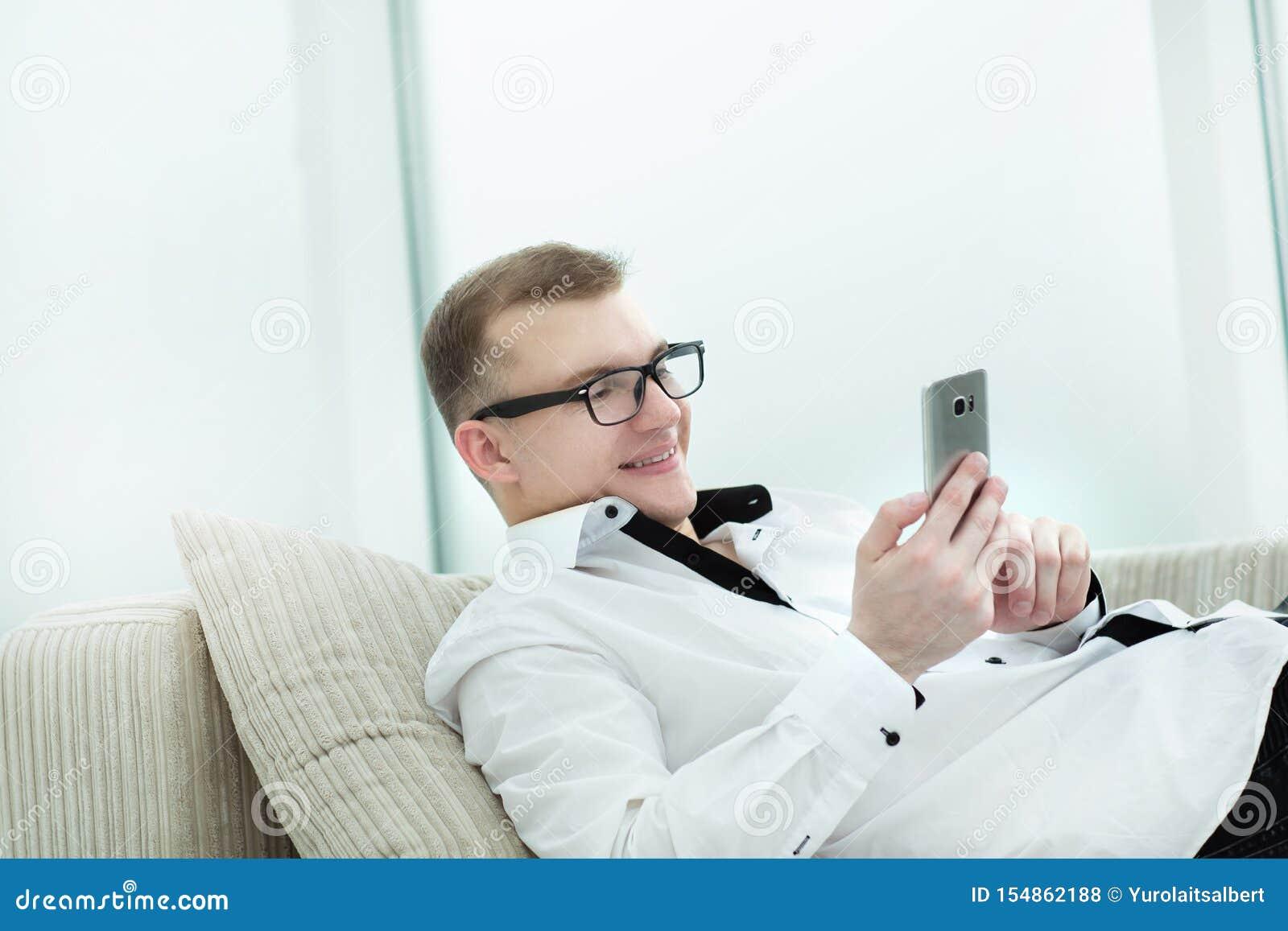 Успешный бизнесмен печатая пока читающ текст на его смартфоне