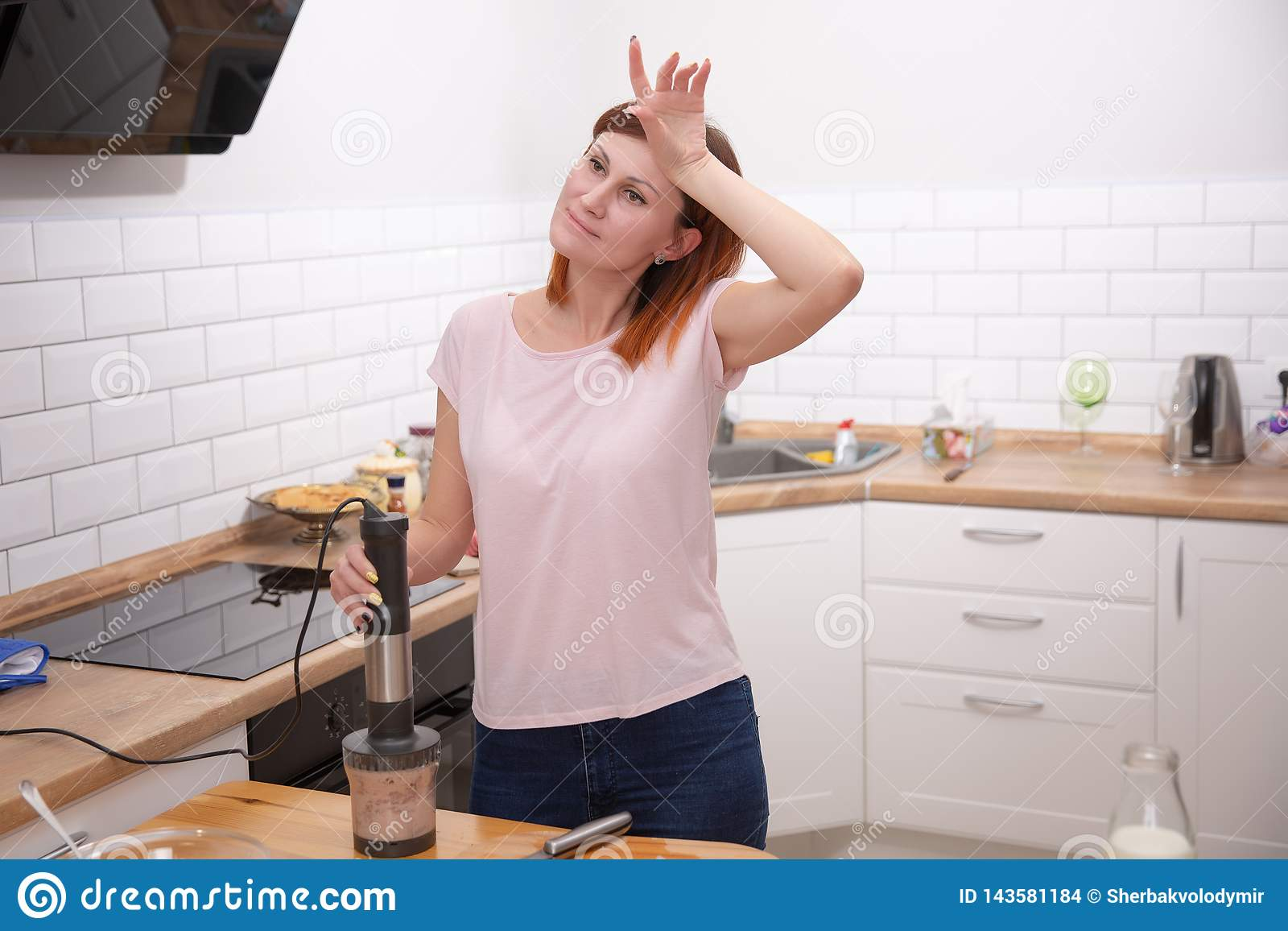 Уставшая домохозяйка полагаясь на кухонном комбайне пока варящ на кухне дома Осложненный рецепт