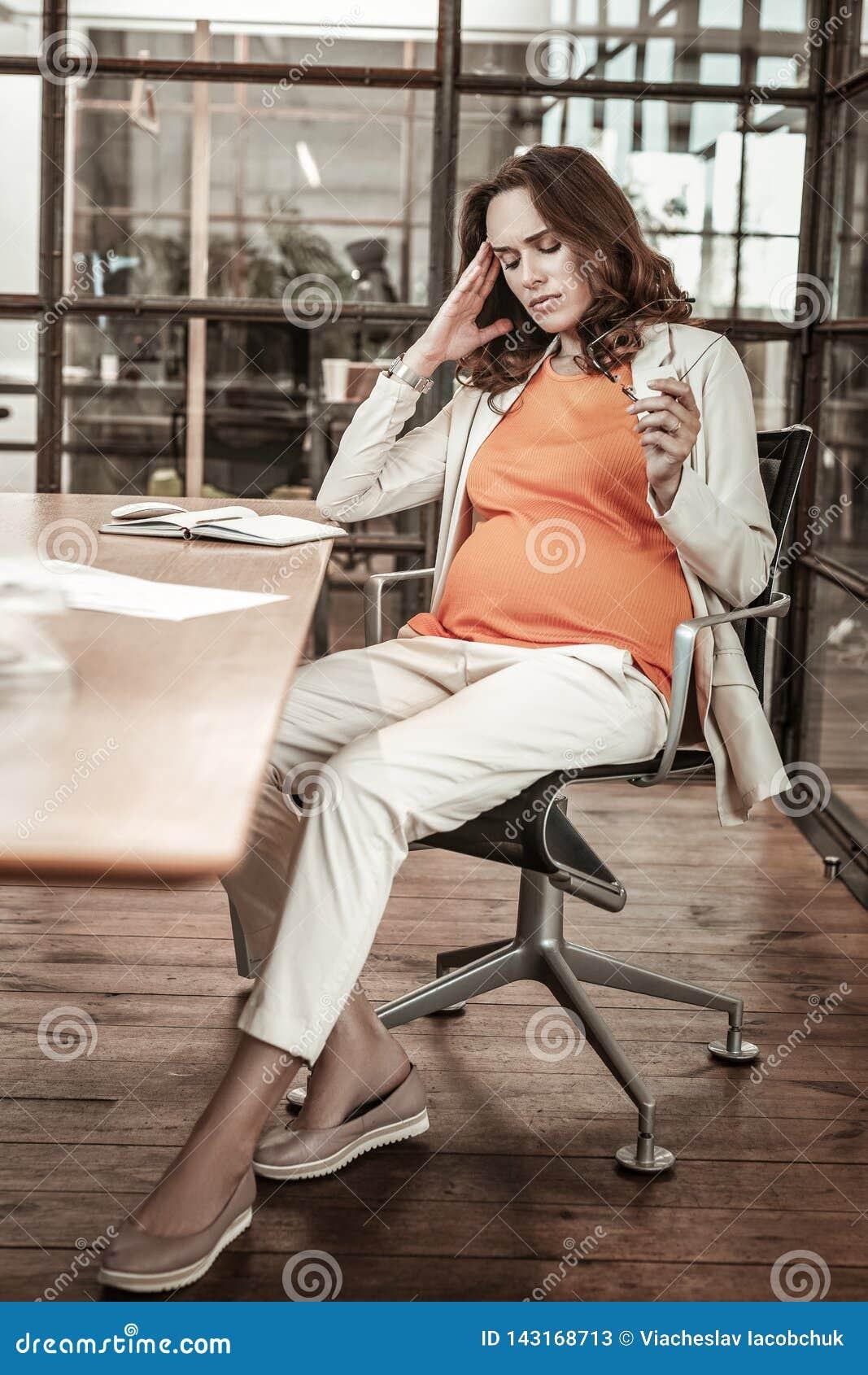 Уставшая симпатичная беременная женщина принимая ее стекла и тереть висок