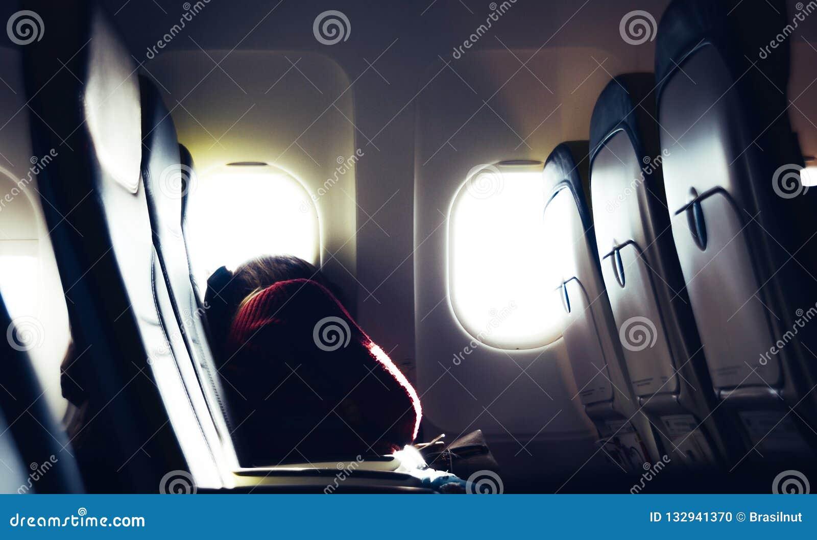 Уставшая случайная неопознаваемая тысячелетняя кавказская молодая женщина napping на месте пока путешествующ самолетом с ярким
