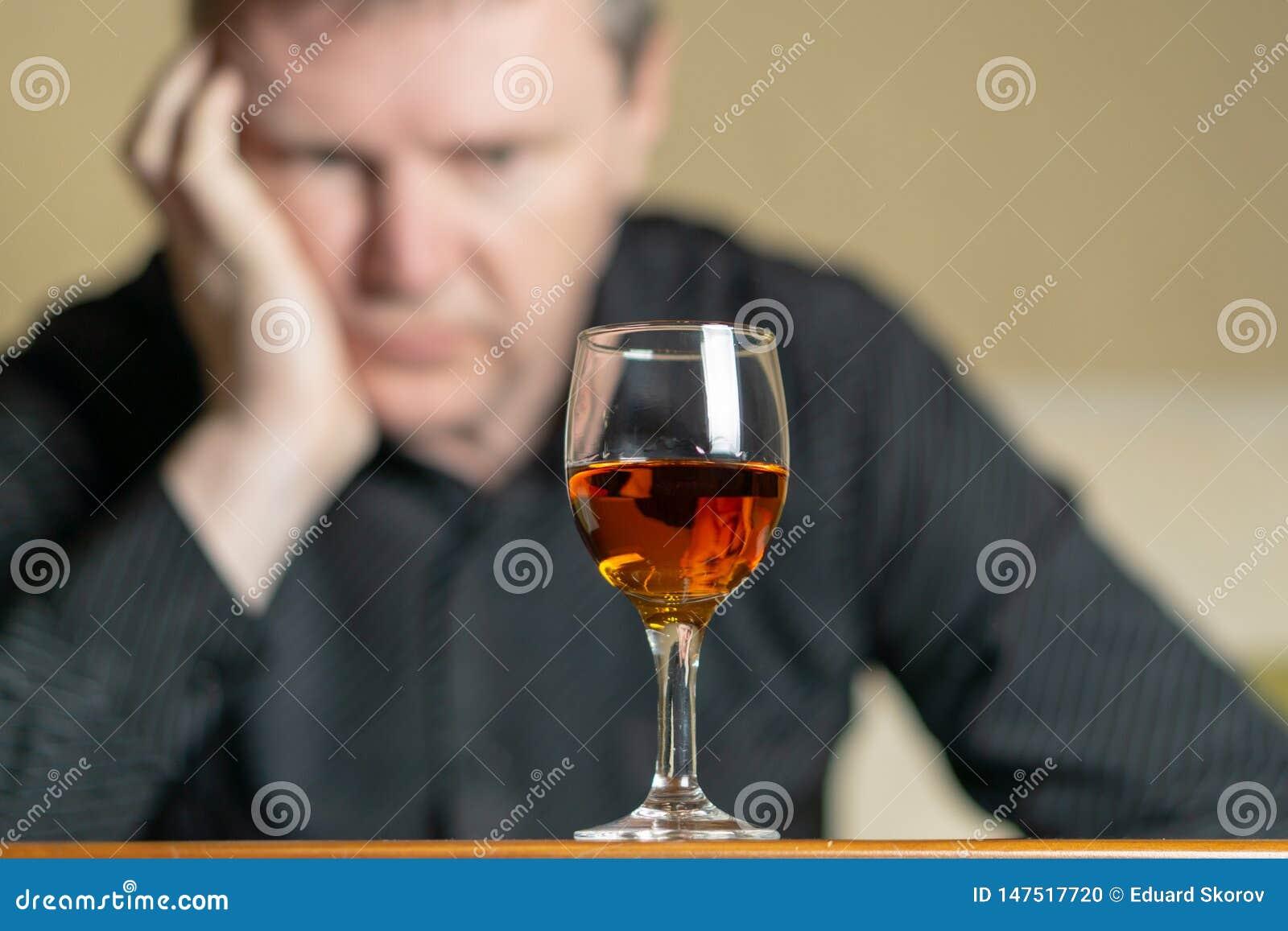 Уставший человек полагаясь его голова на стекле рябиновки Человек из фокуса