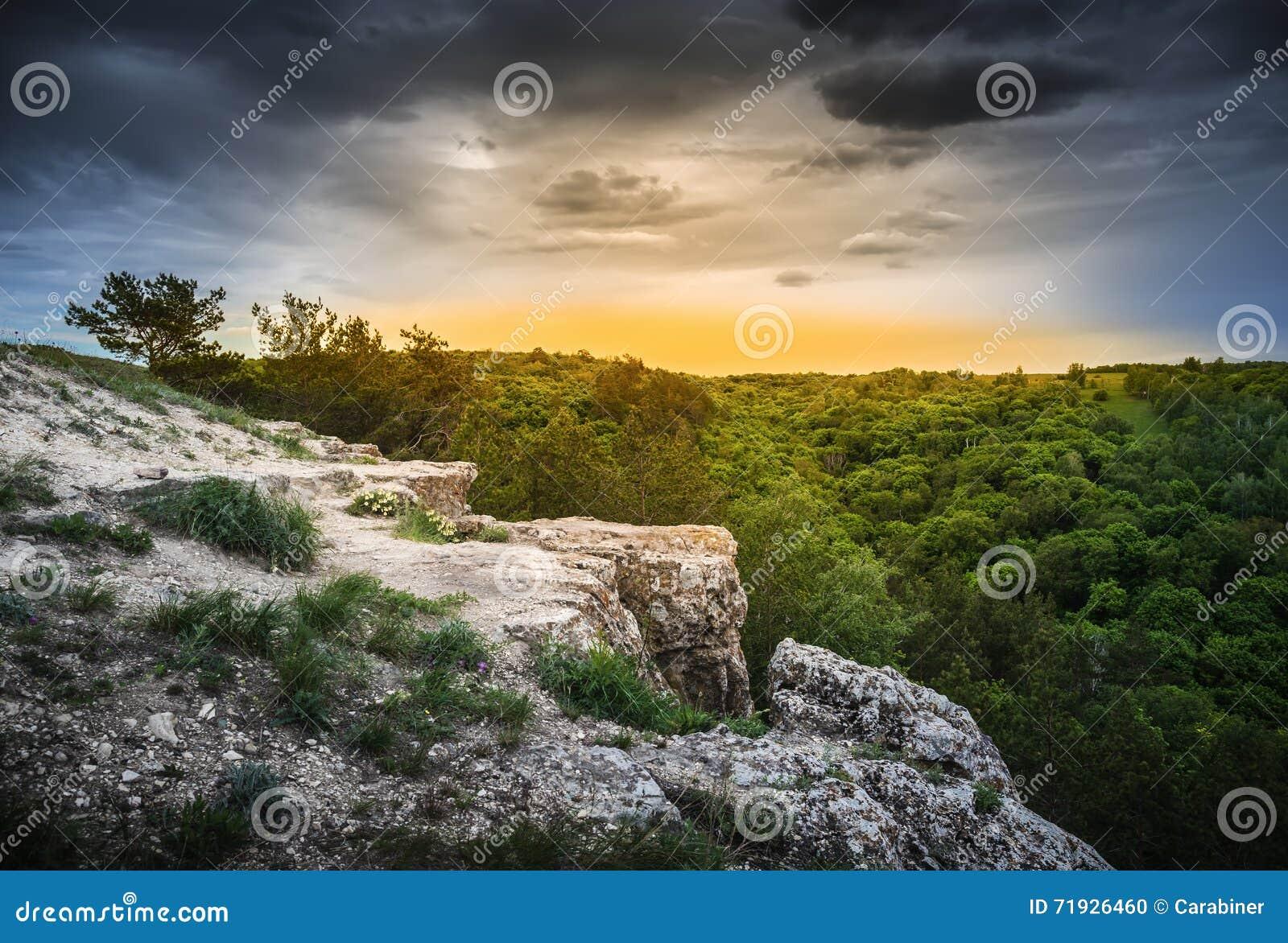 Уступ утеса в лесистых горах на зоре