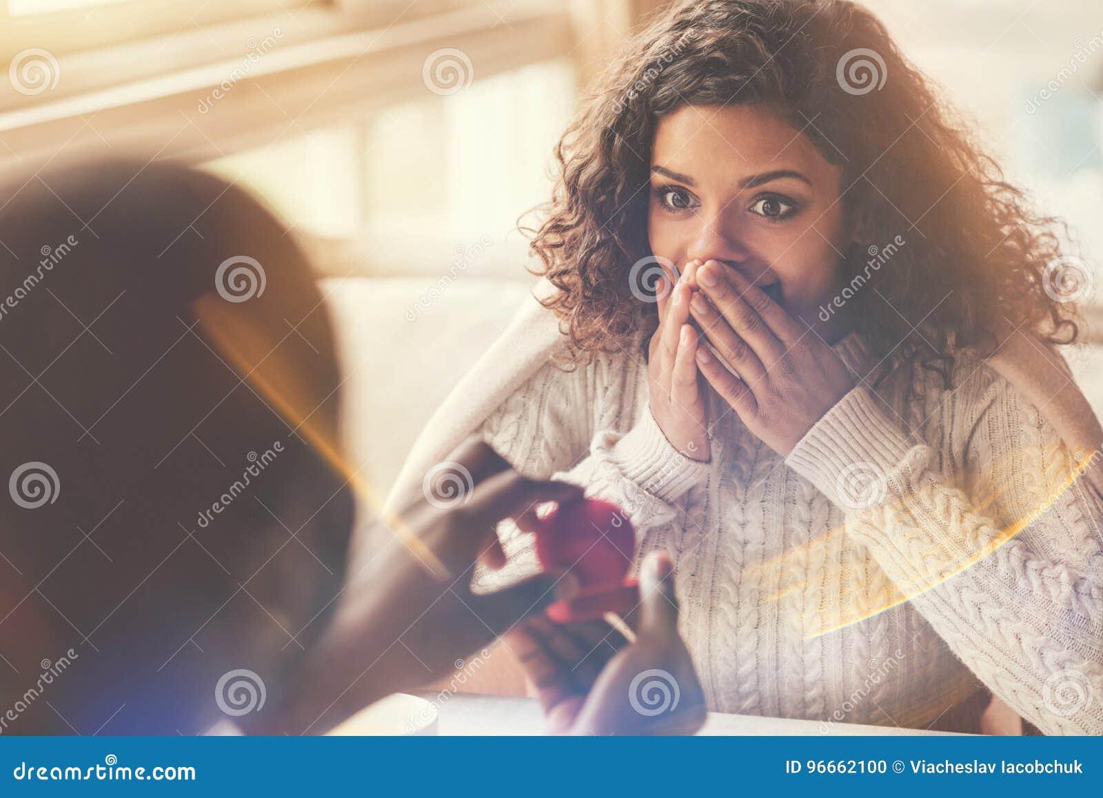 Услаженная счастливая женщина смотря обручальное кольцо