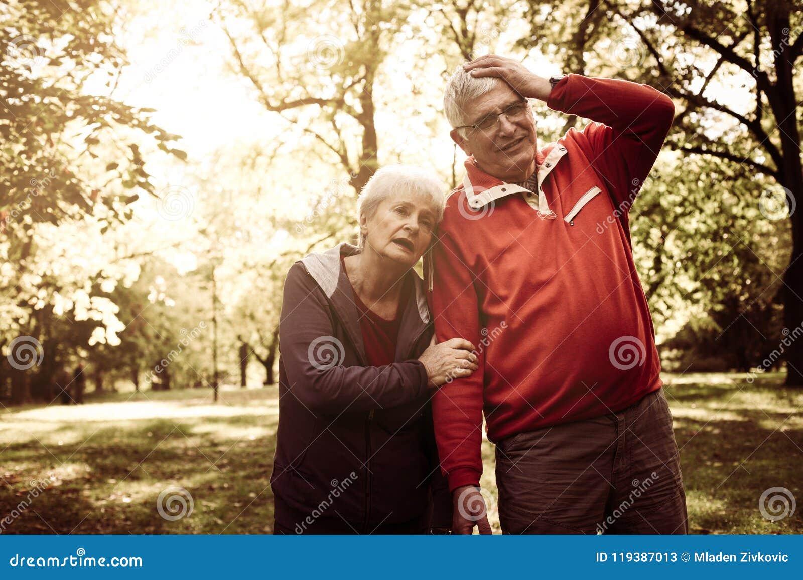 Утомленные старшие пары стоя в парке после тренировки