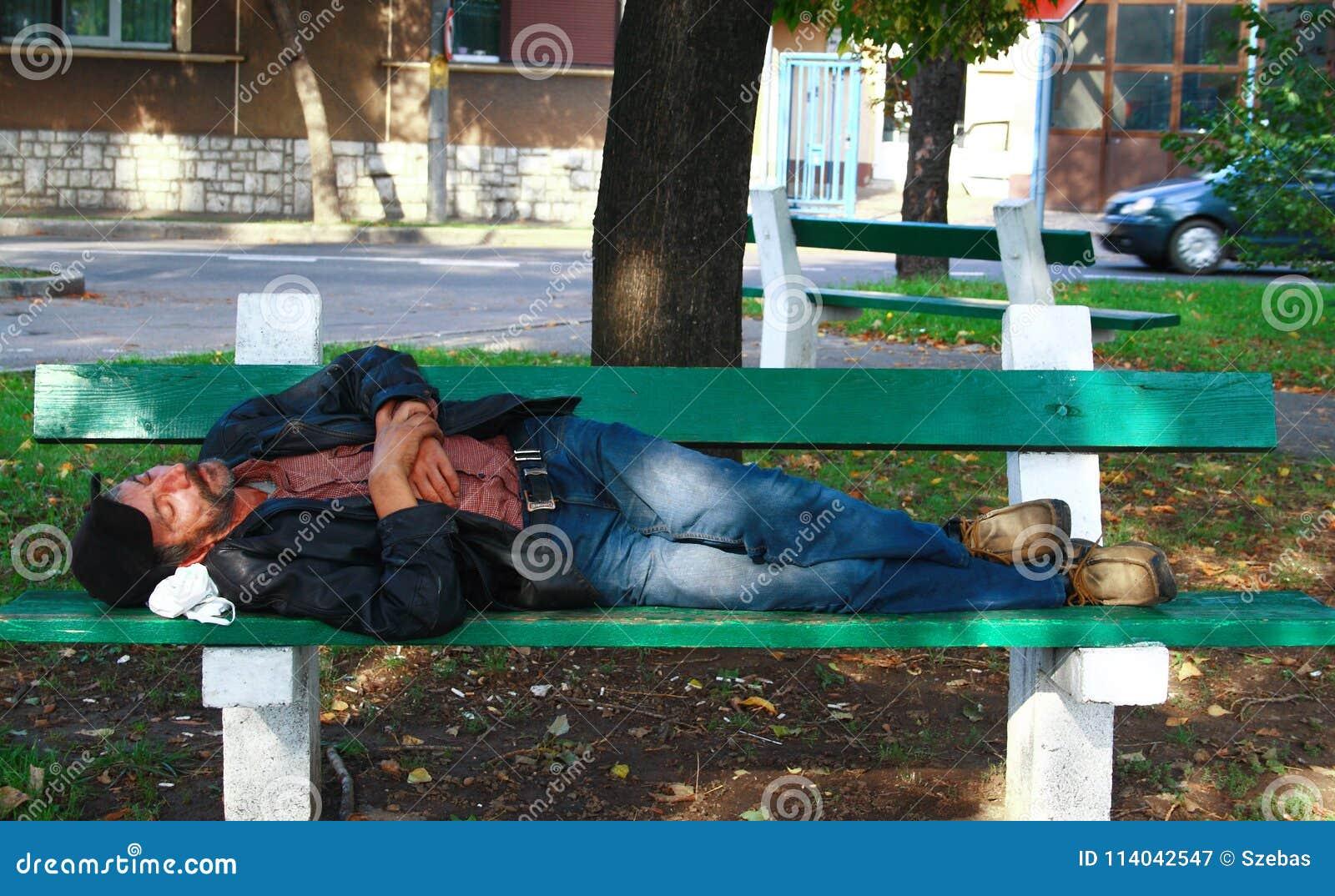 Утомленный бездомный человек спать на стенде