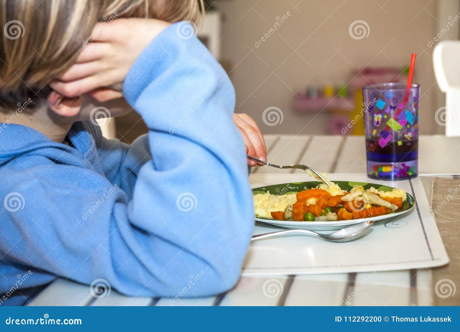 Утомленный мальчик не любит съесть его обед