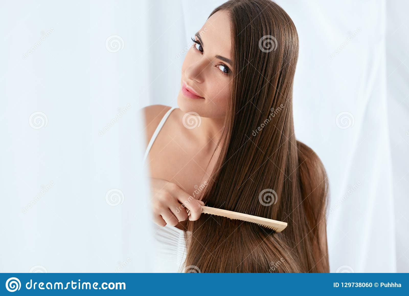 Уход за волосами красоты Красивая женщина расчесывая длинные естественные волосы