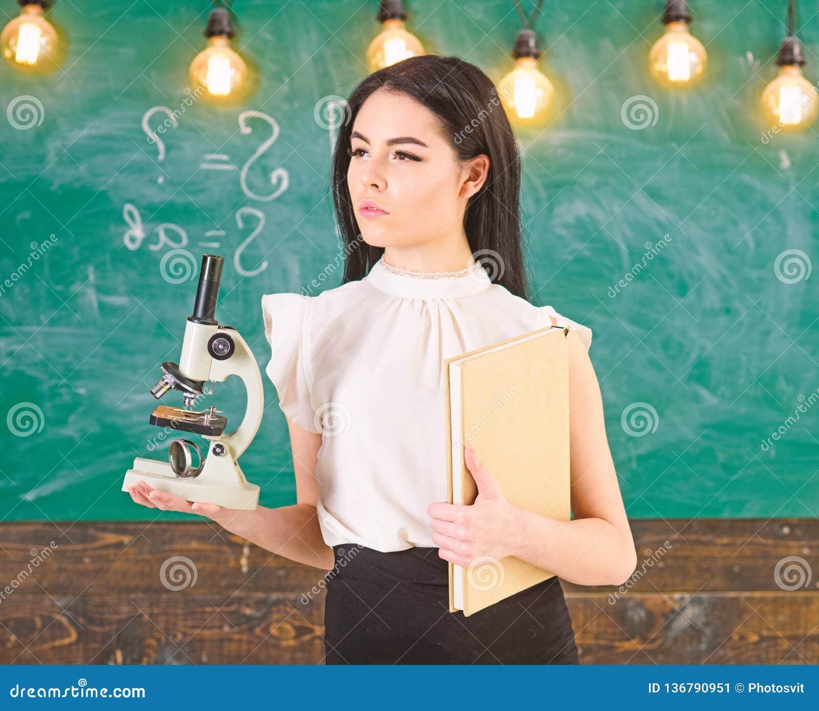 Ученый дамы держит книгу и микроскоп, доску на предпосылке, космосе экземпляра Дама в официально носке на спокойной стороне внутр