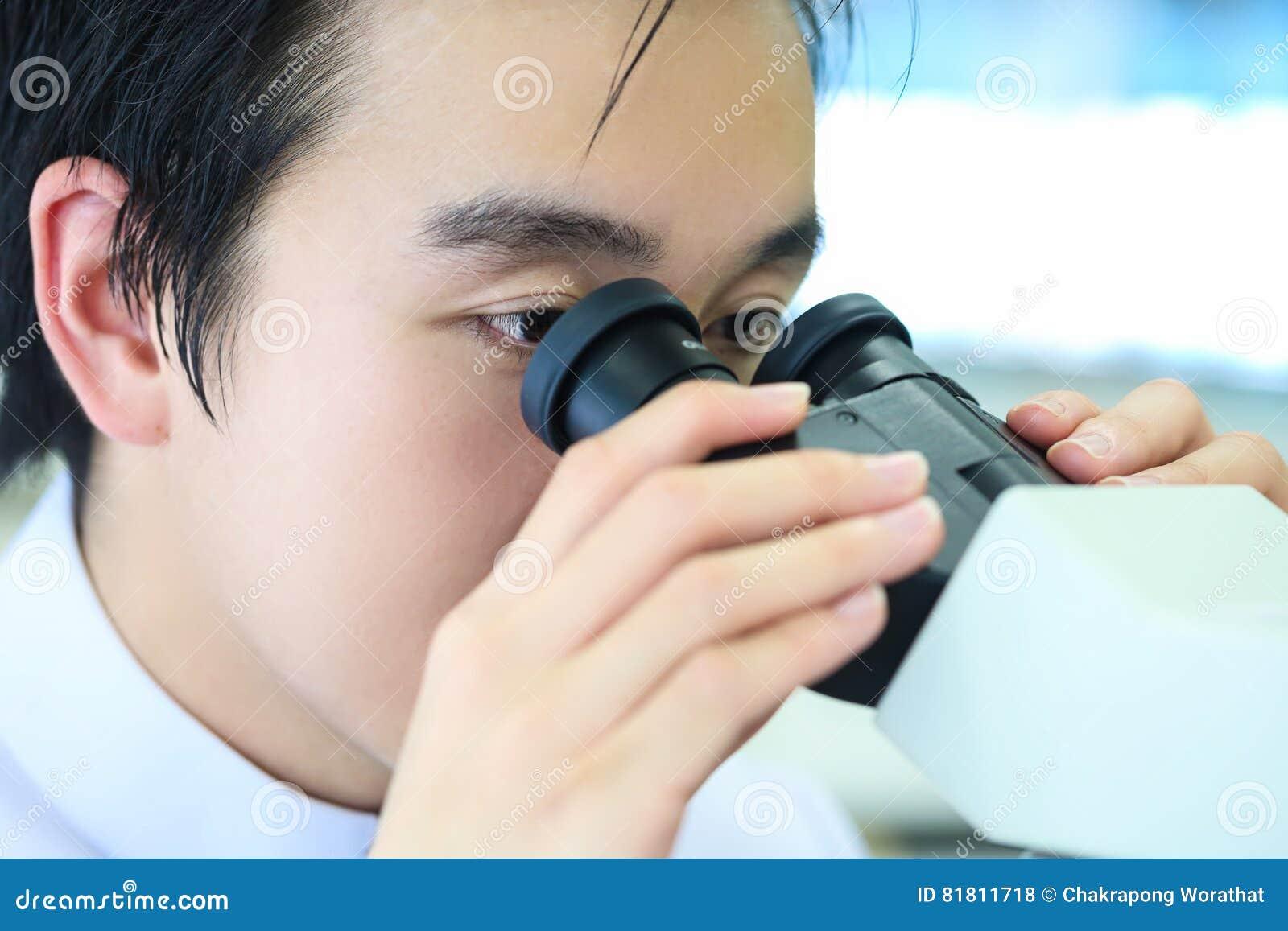 Ученый используя микроскоп на работе в лаборатории