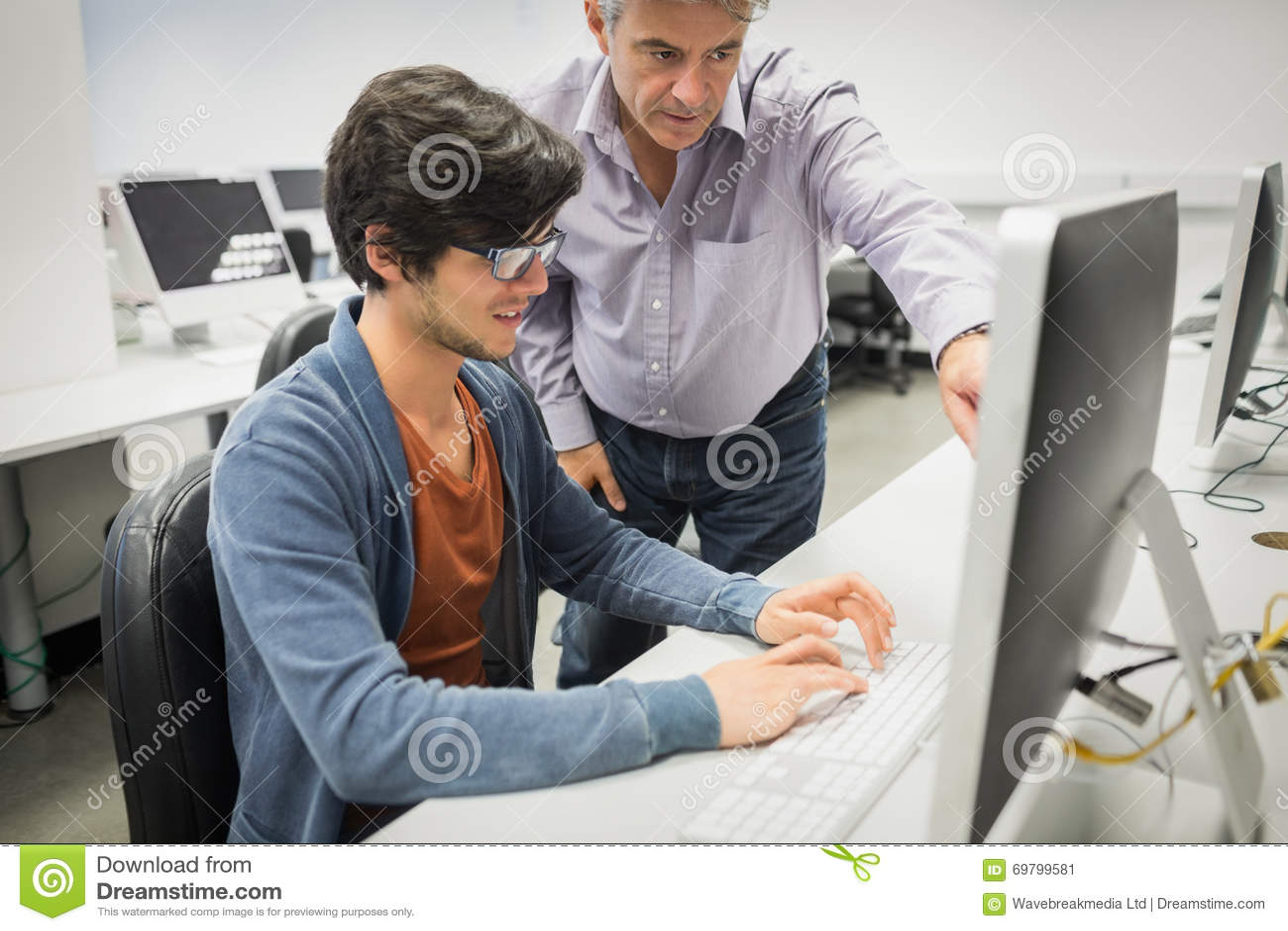 Учитель компьютера помогая студенту