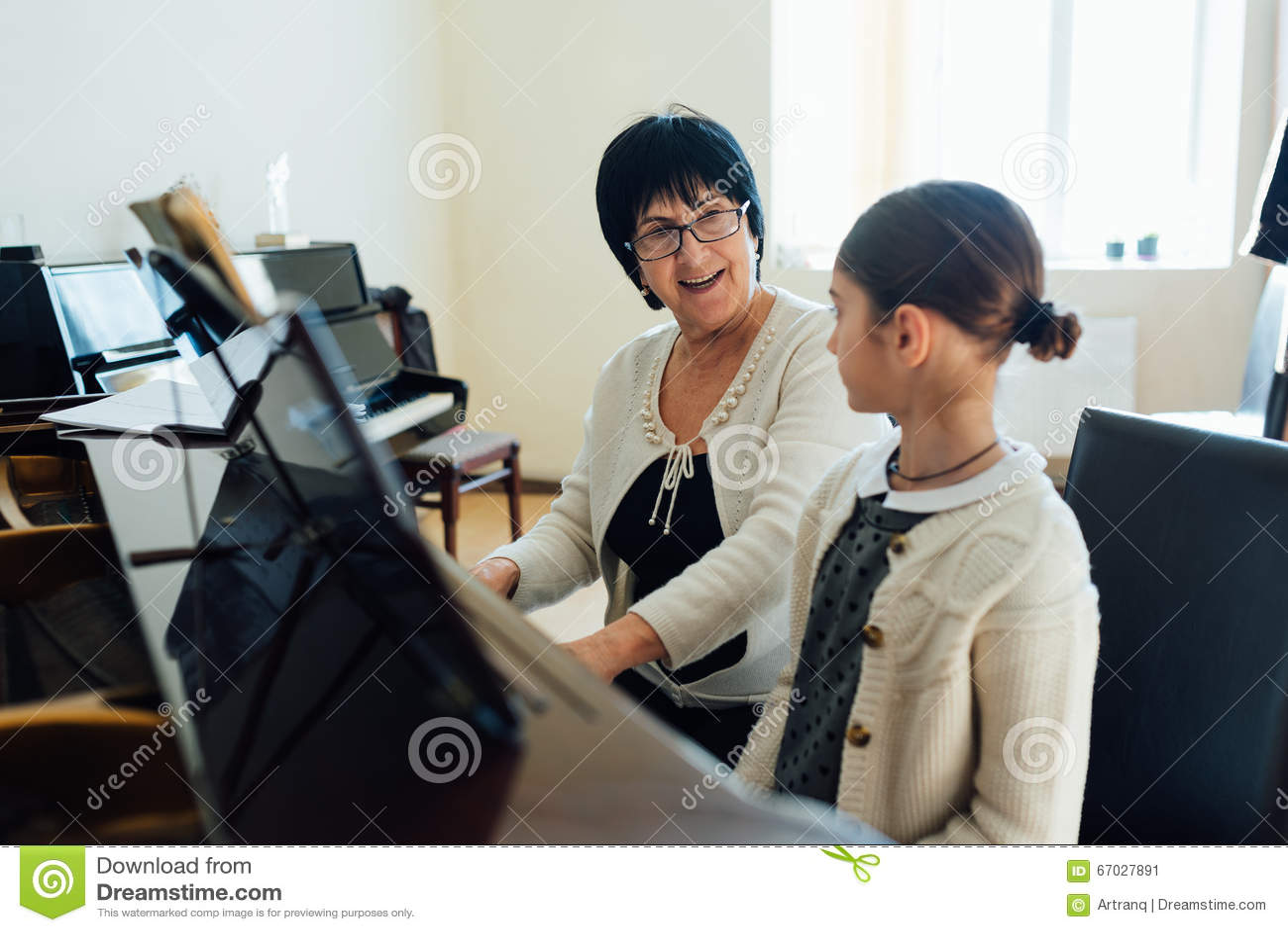 Учитель музыки объясняет gleefully как сыграть рояль