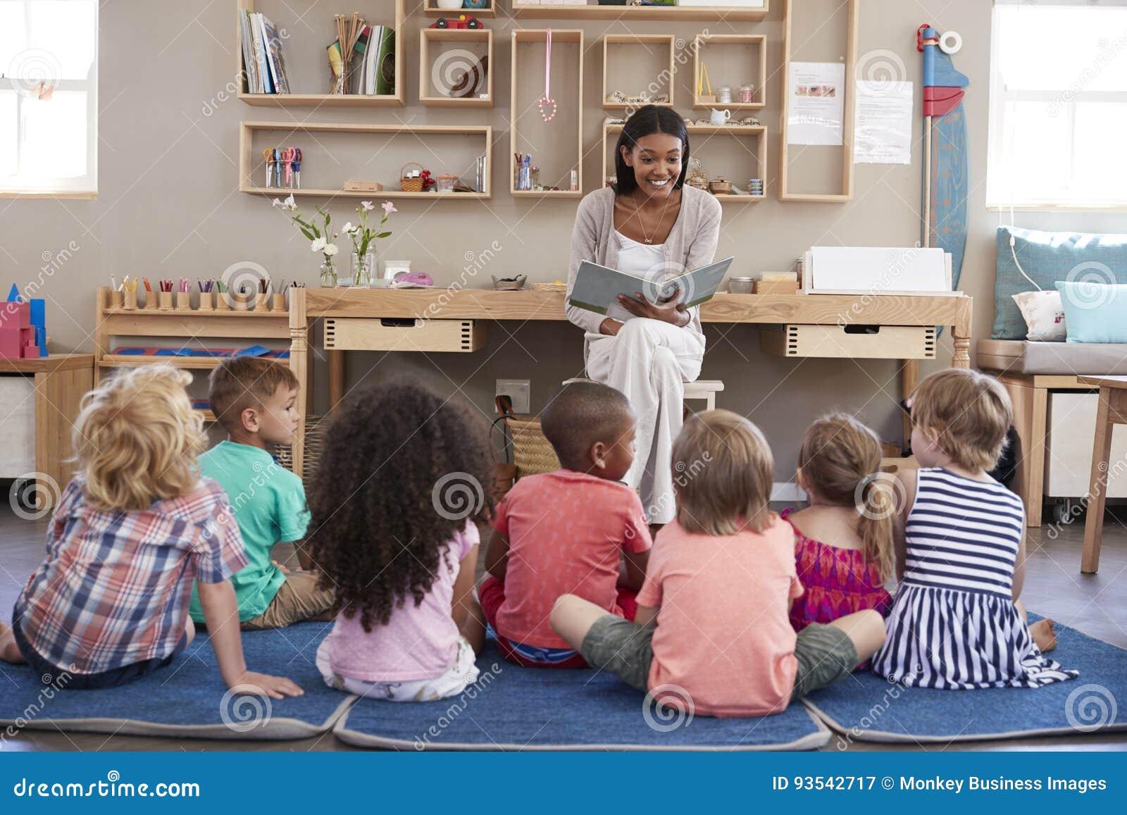 Учитель на школе Montessori читая к детям на времени рассказа