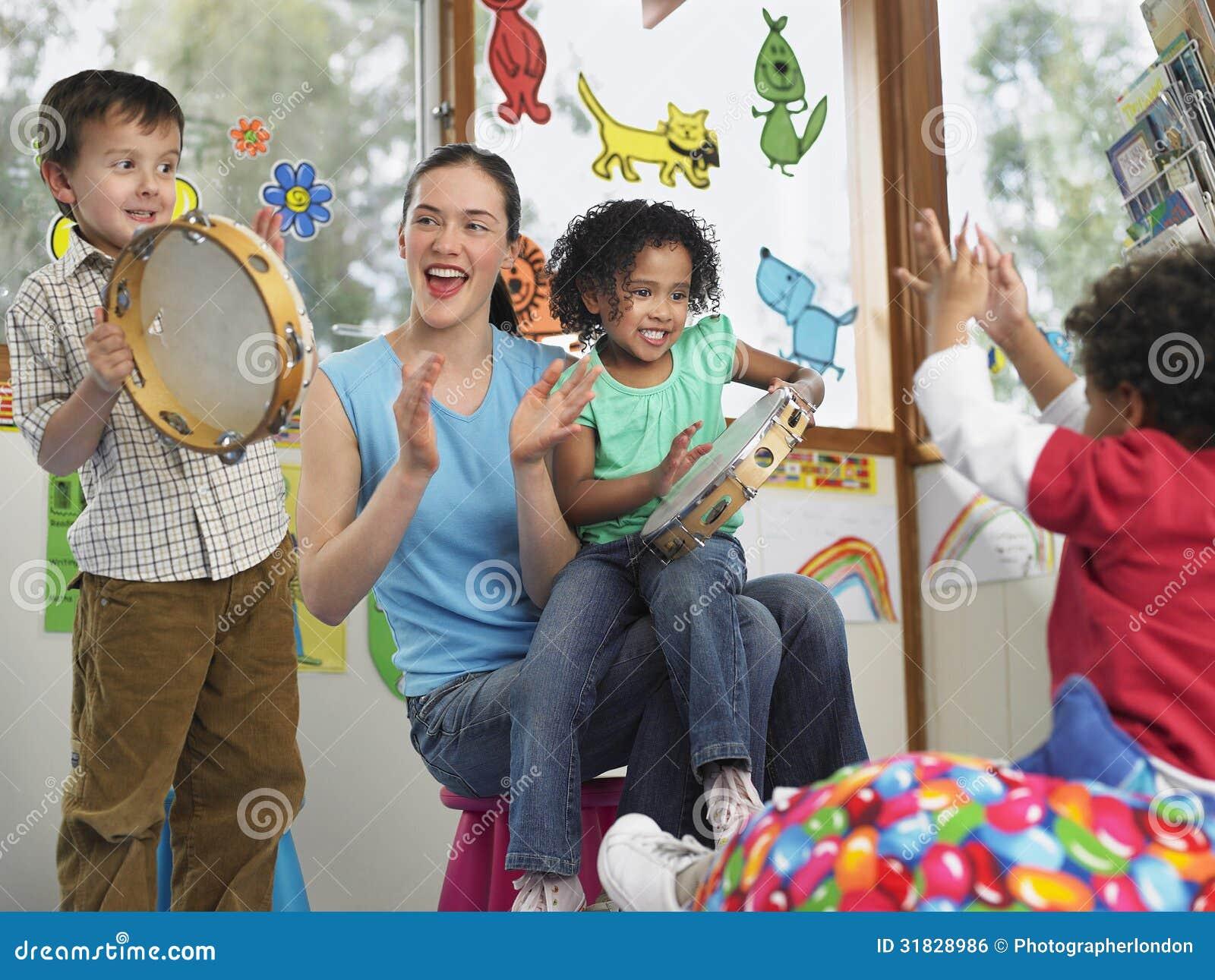 Учитель при дети играя музыку в классе