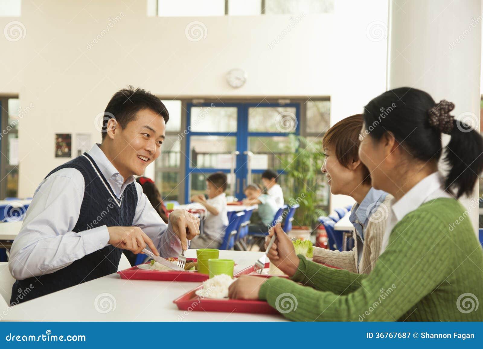 Учителя говоря на обеде в школьном кафетерии