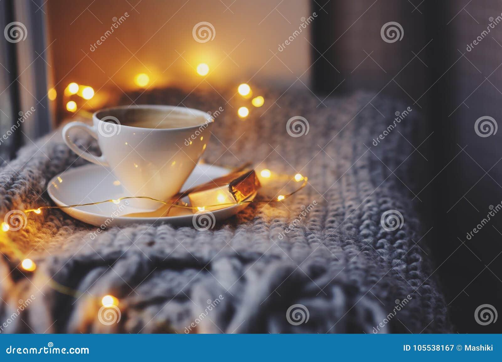 Уютное утро зимы или осени дома Горячий кофе с ложкой золота металлической, греет света одеяла, гирлянды и свечи