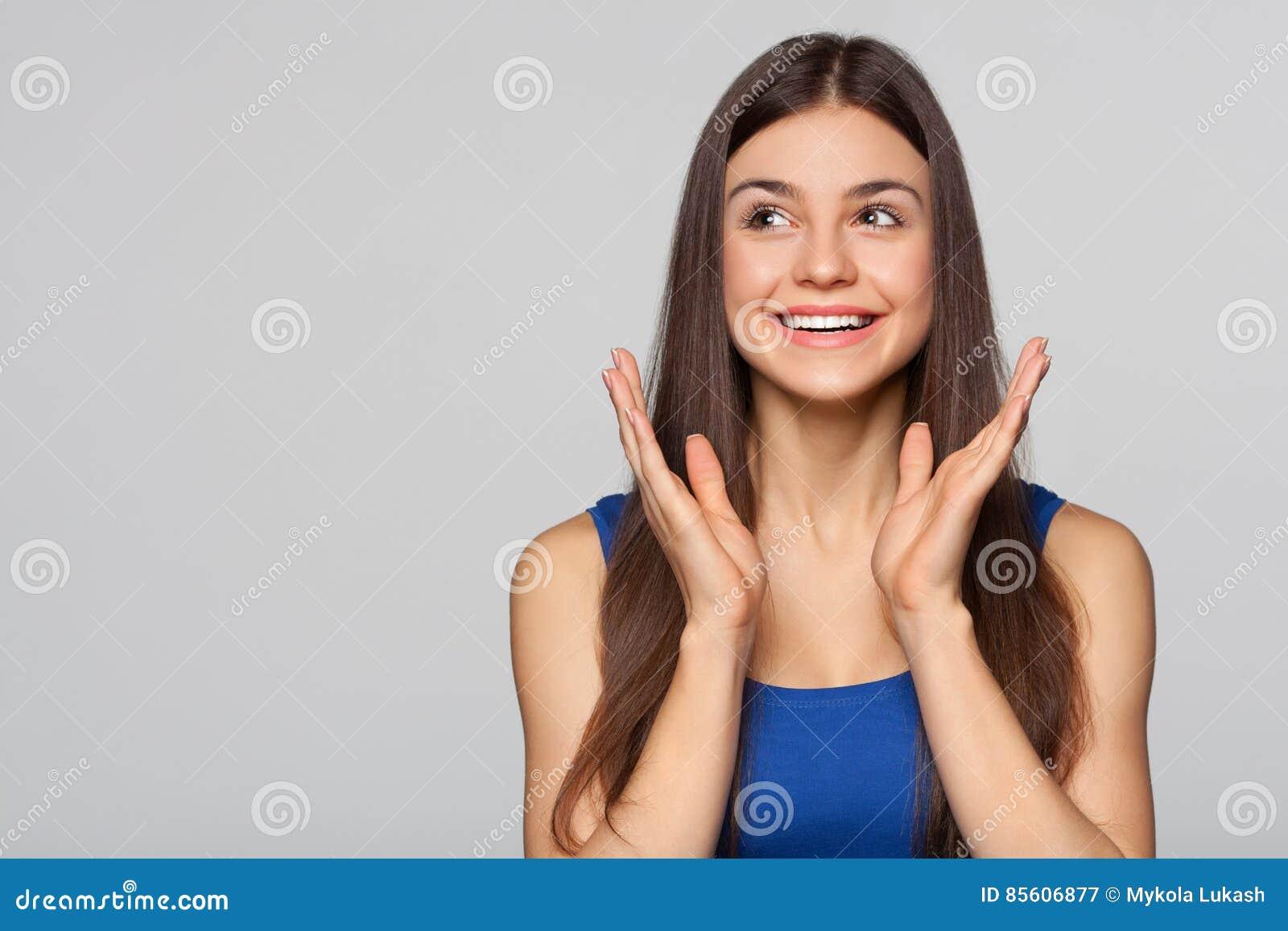 Удивленная счастливая красивая женщина смотря косой в ободрении, изолированном на серой предпосылке