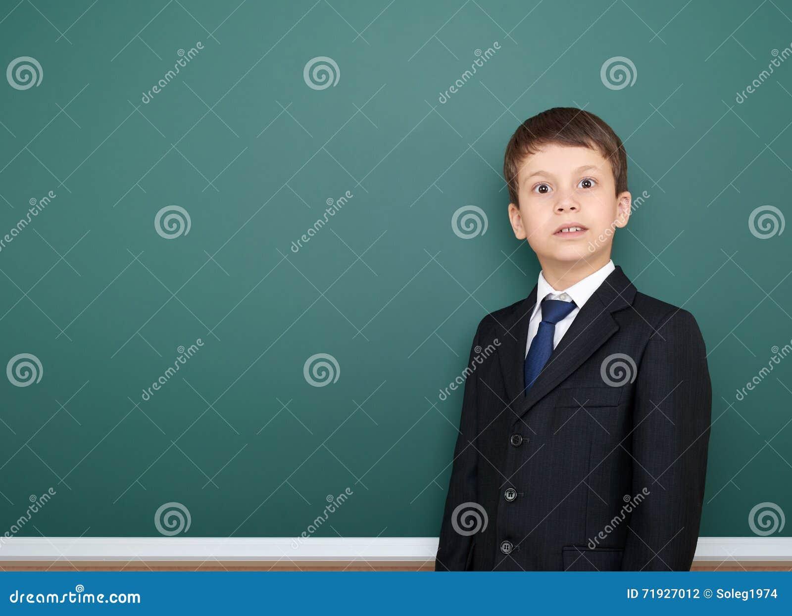 Удивленный школьник в черном портрете костюма на зеленой предпосылке доски, концепции образования
