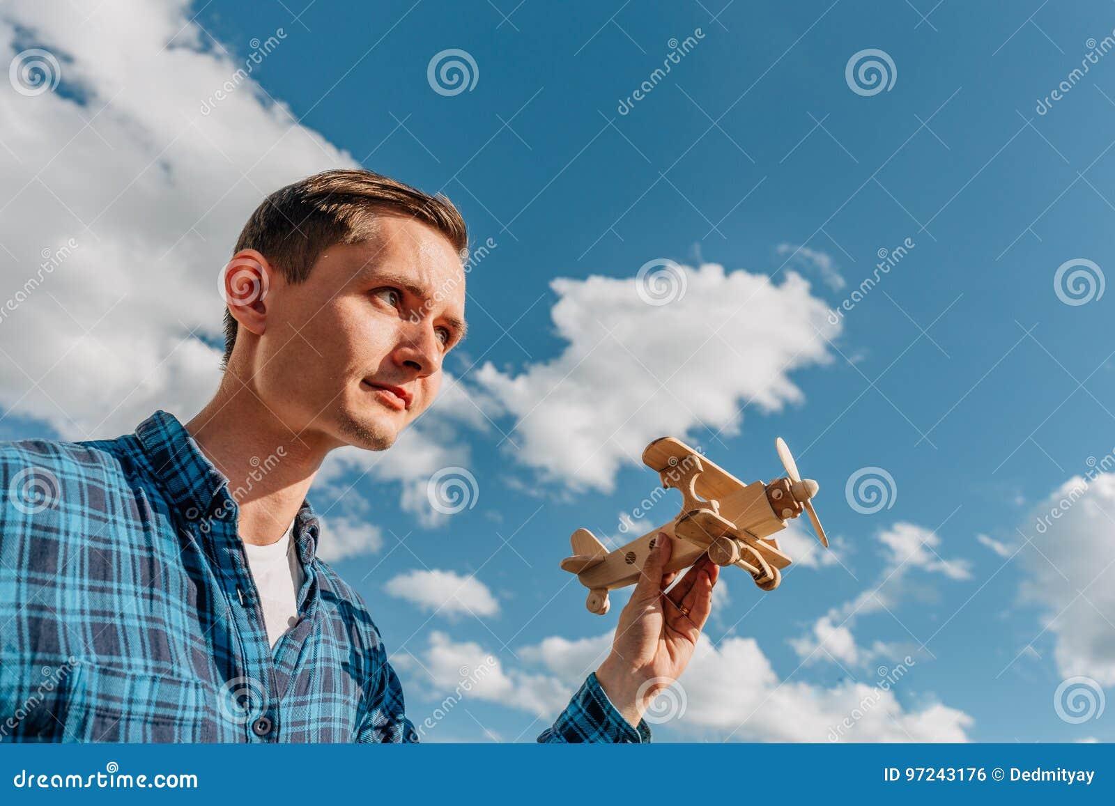 Фантазер, молодой человек держа в самолете игрушки руки деревянном на предпосылке голубого неба с космосом экземпляра