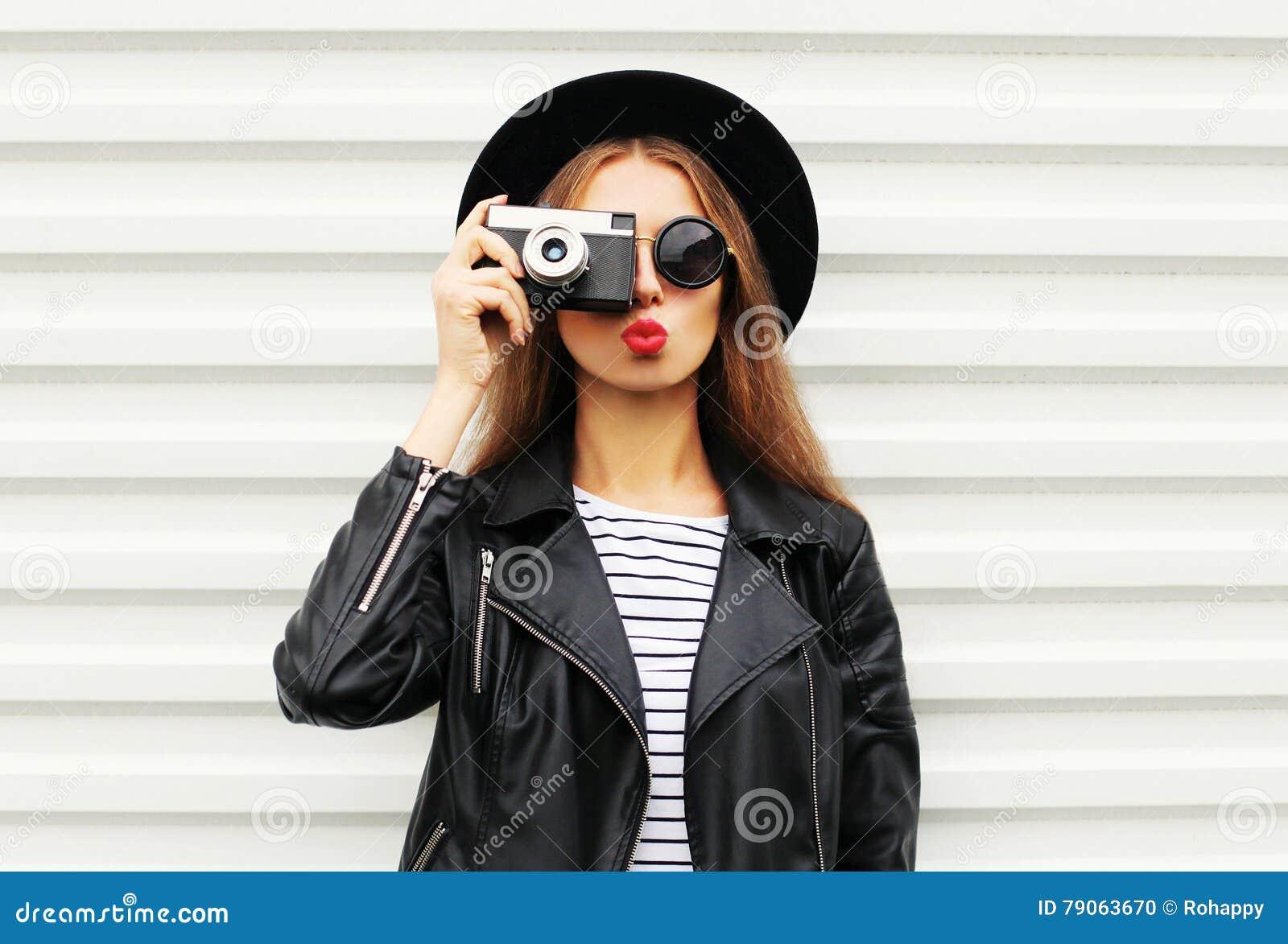 Фасонируйте взгляд, довольно холодную модель молодой женщины при ретро камера фильма нося элегантную черную шляпу, кожаную куртку