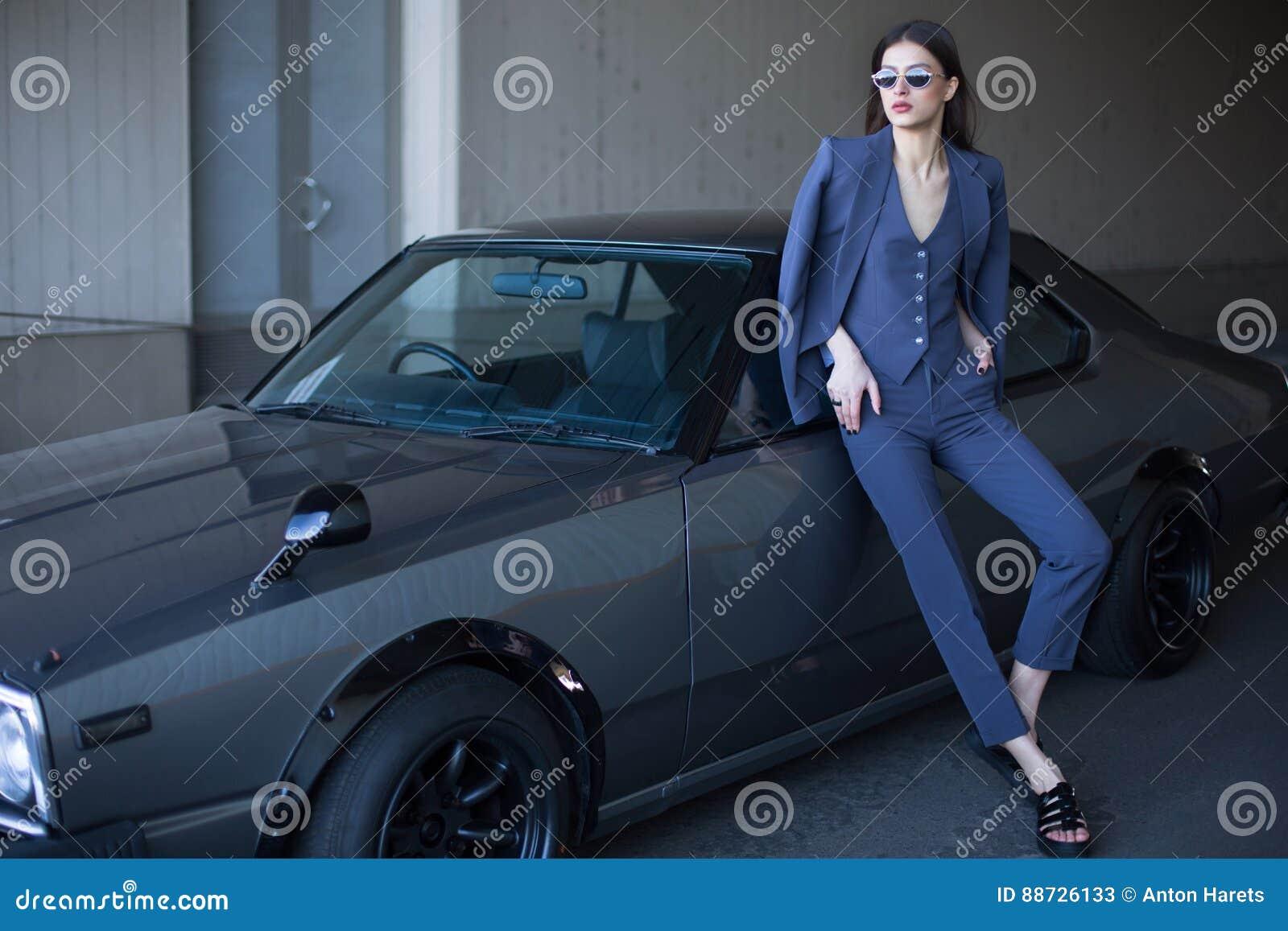 Фасонируйте девушку стоя рядом с ретро спортивной машиной на солнце Стильная женщина в сером костюме ждать около классического ав