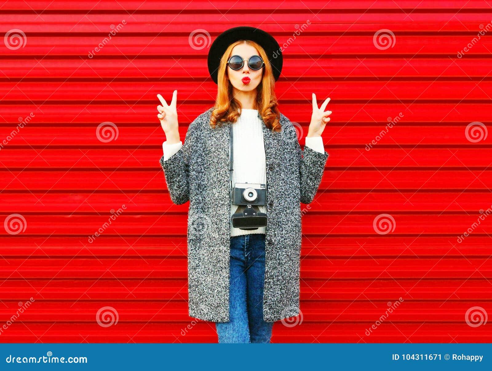 Фасонируйте портрету милую женщину при ретро камера представляя на красном цвете