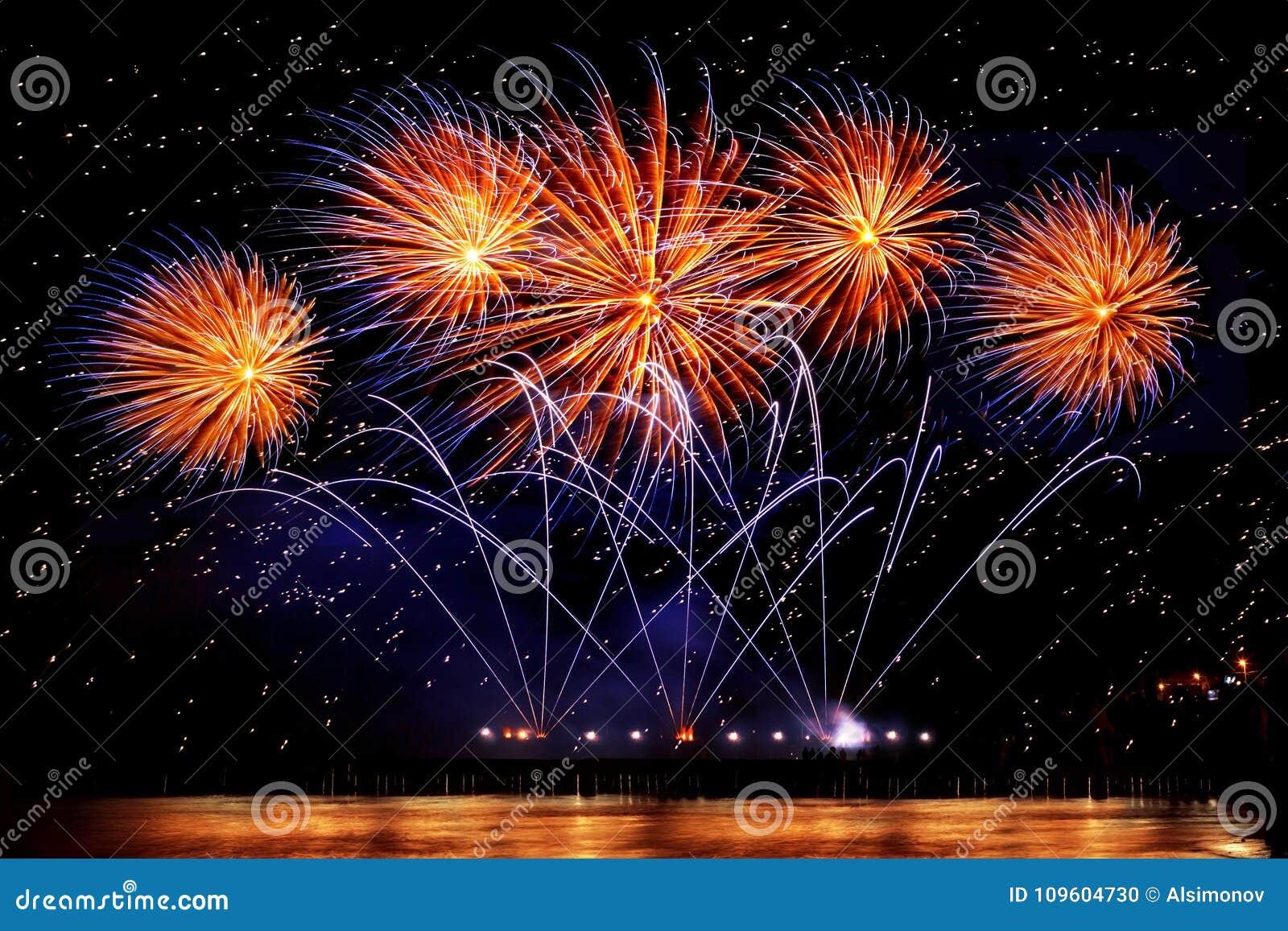 Фейерверки праздника золотого цвета на черной предпосылке неба