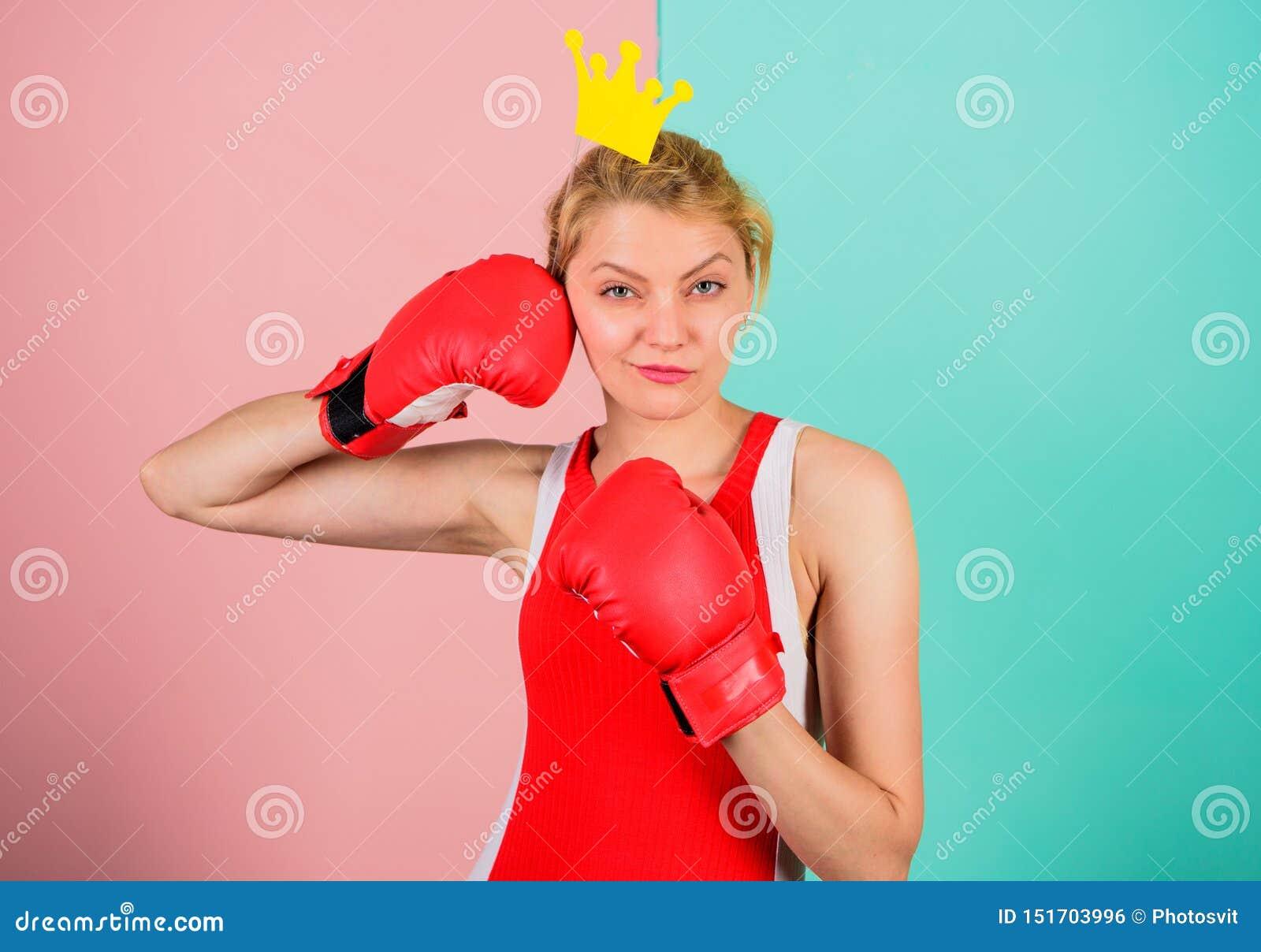 Ферзь спорта Станьте самый лучший в спорте бокса Женственная нежная блондинка с кроной ферзя носит перчатки бокса Воевать для
