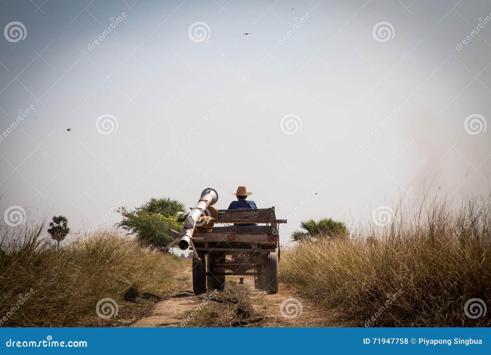 Фермер идет назад домой после трудной работы на сером небе