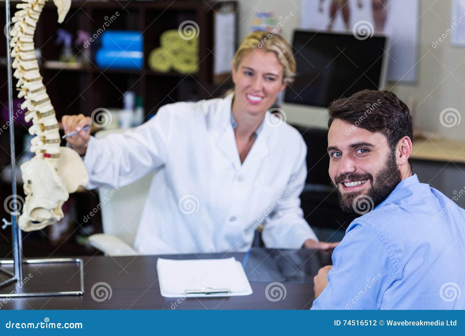 Физиотерапевт объясняя модель позвоночника к пациенту