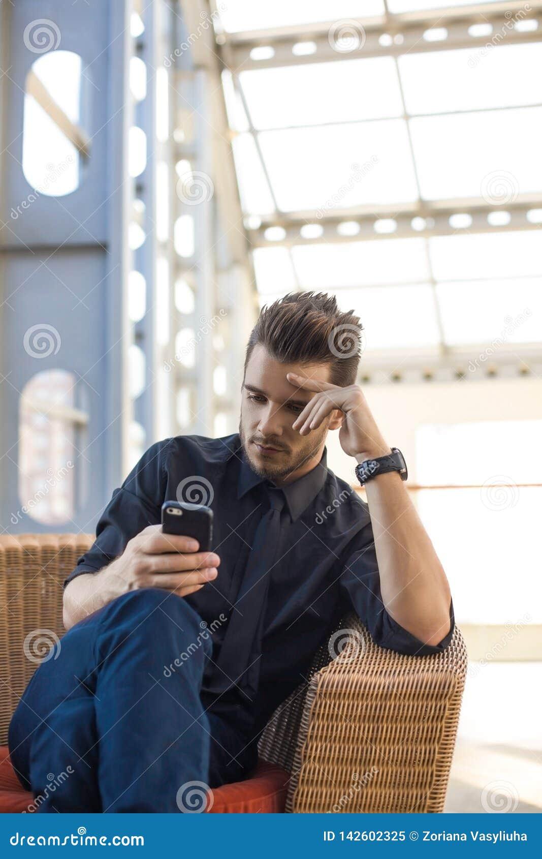 Финансовые новости внимательного мужского главного исполнительного директора читая на вебсайте через мобильный телефон во время п