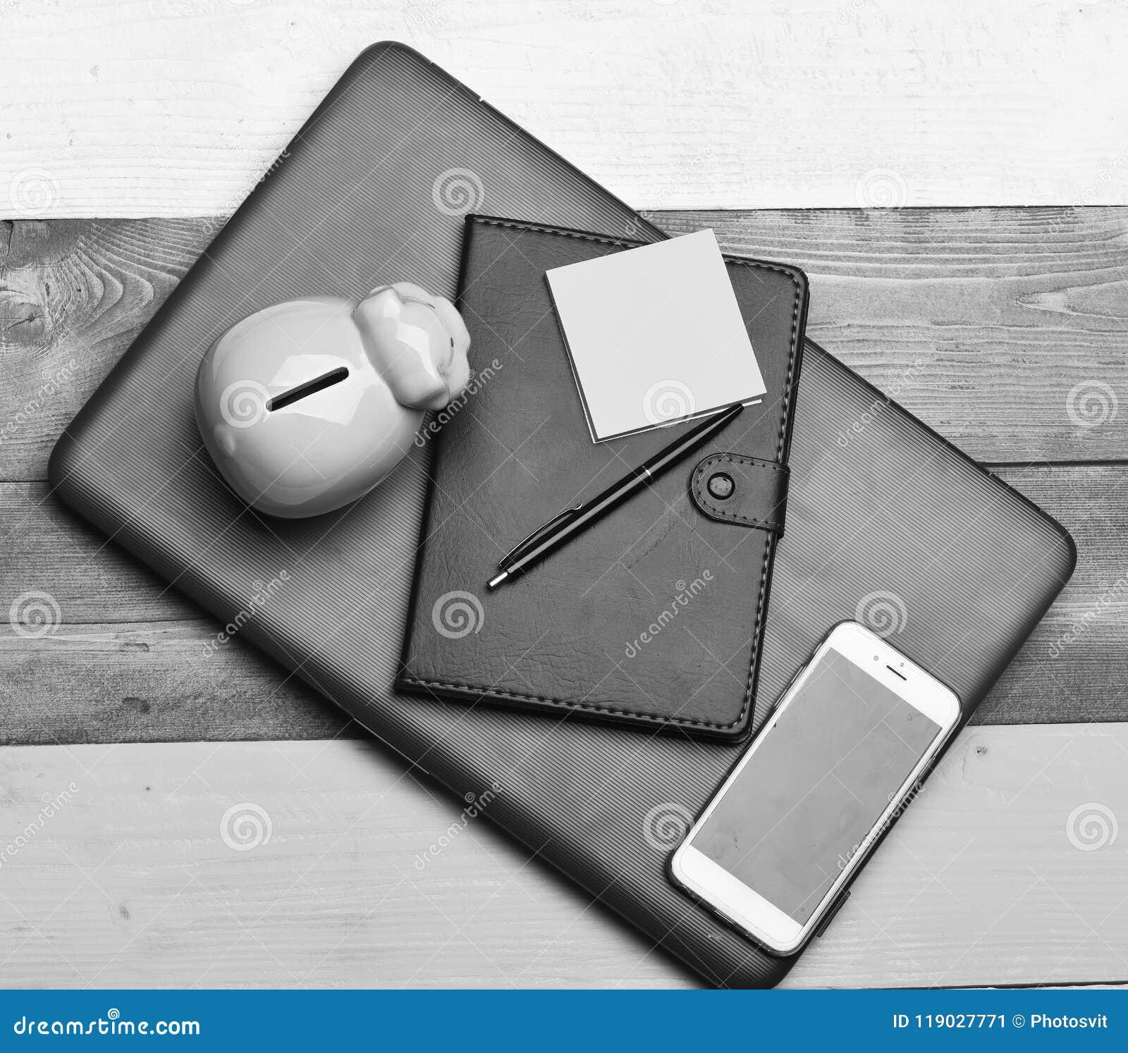 Финансы и концепция бюджета Состав домашнего офиса Moneybox около организатора, ручки, липких примечаний, телефона