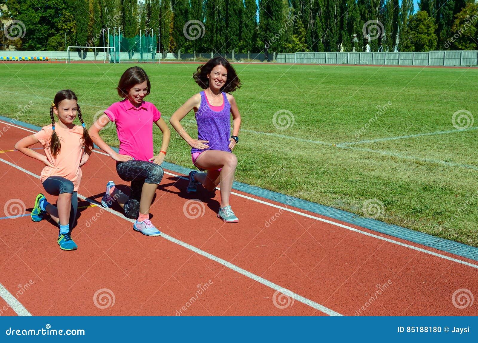 Фитнес, мать и дети семьи тренируя на стадионе, спорте с детьми