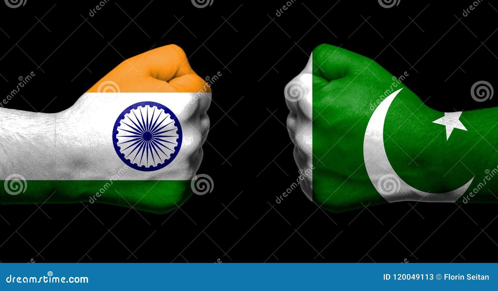 Флаги Индии и Пакистана покрашенных на 2 сжатых кулаках смотря на один другого на черной концепции предпосылки/отношений Индии -