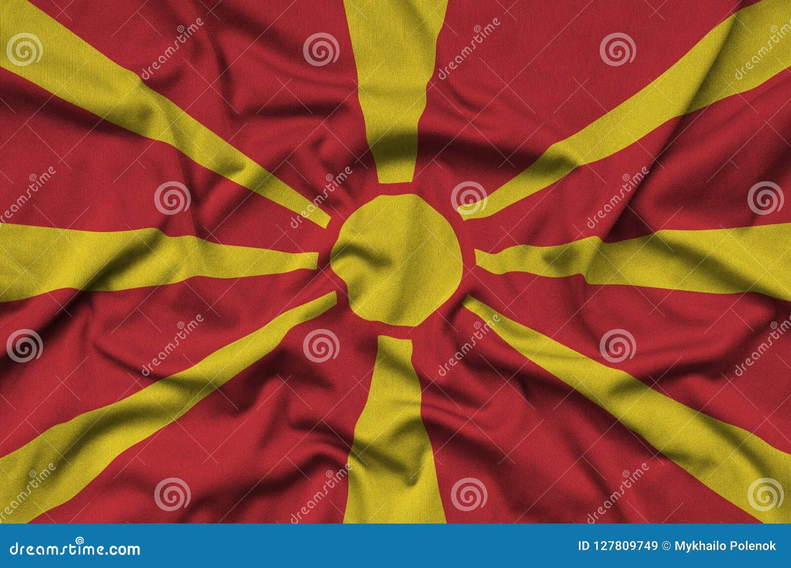 Флаг македонии показан на ткани ткани спорт с много створок Знамя команды спорта