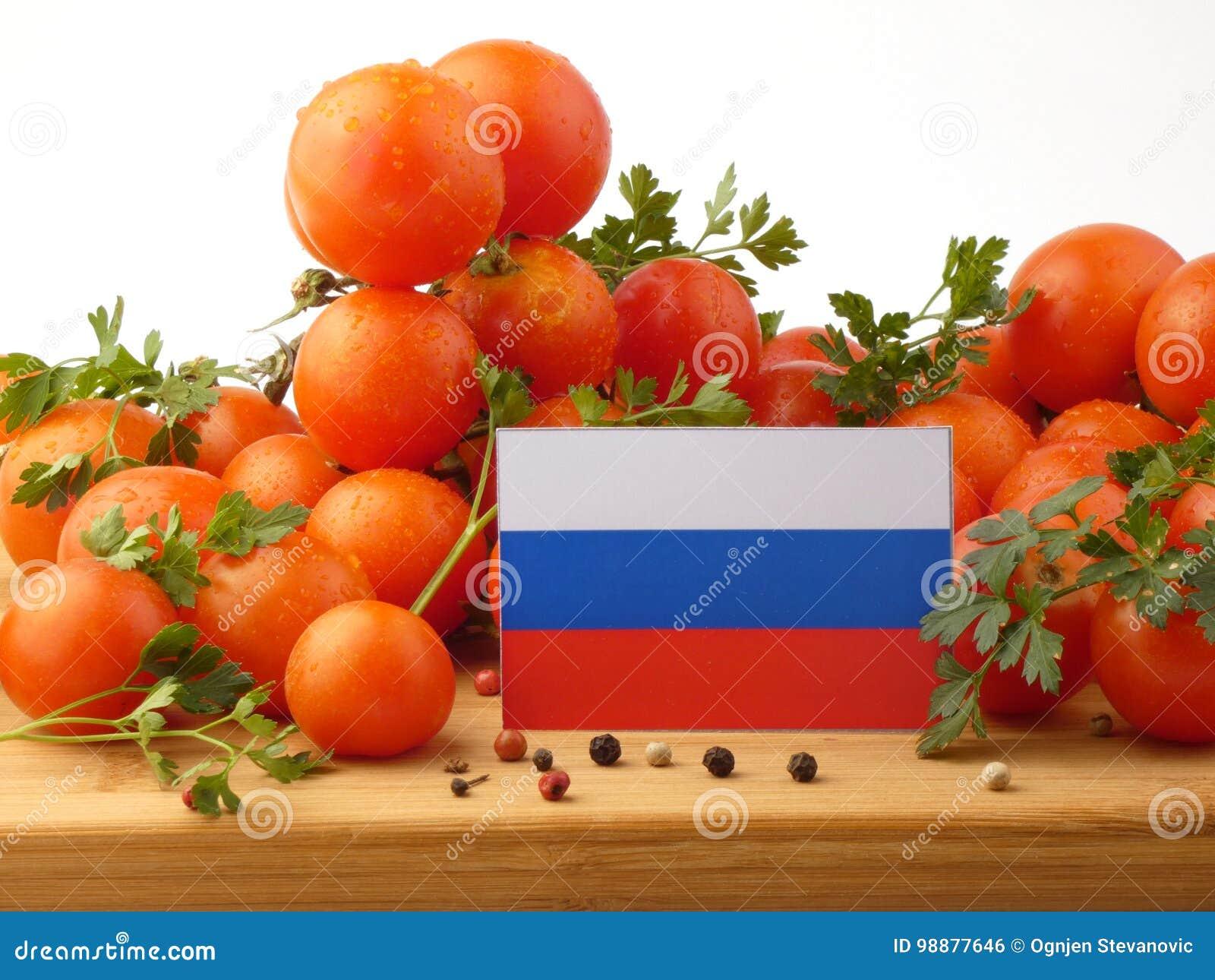 Флаг России на деревянной панели при томаты изолированные на белизне