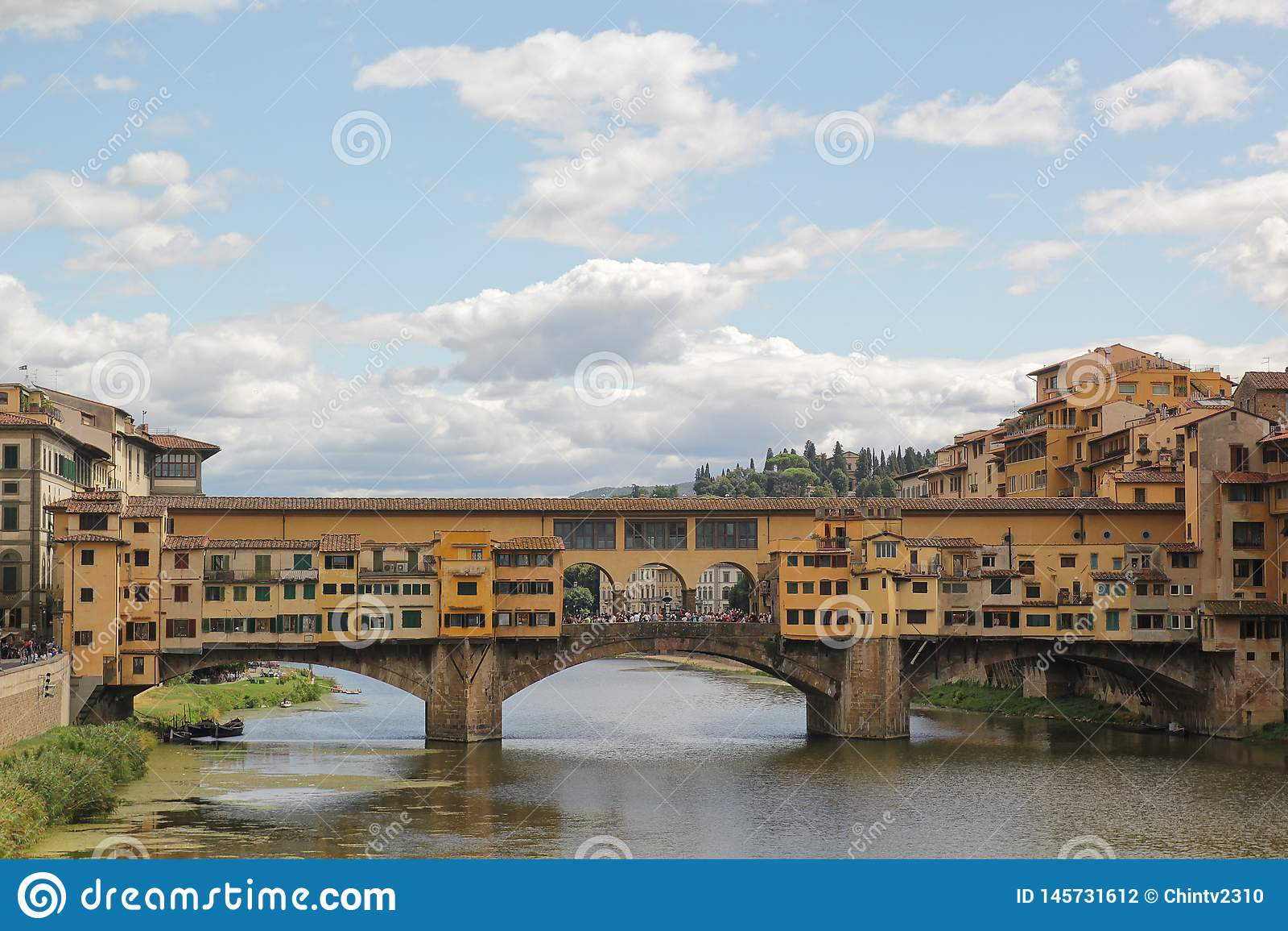 Флоренс, Италия - 03,2017 -го сентябрь: Красивый вид вниз по течению к невесте Ponte Vecchio старой в голубом небе и облаке
