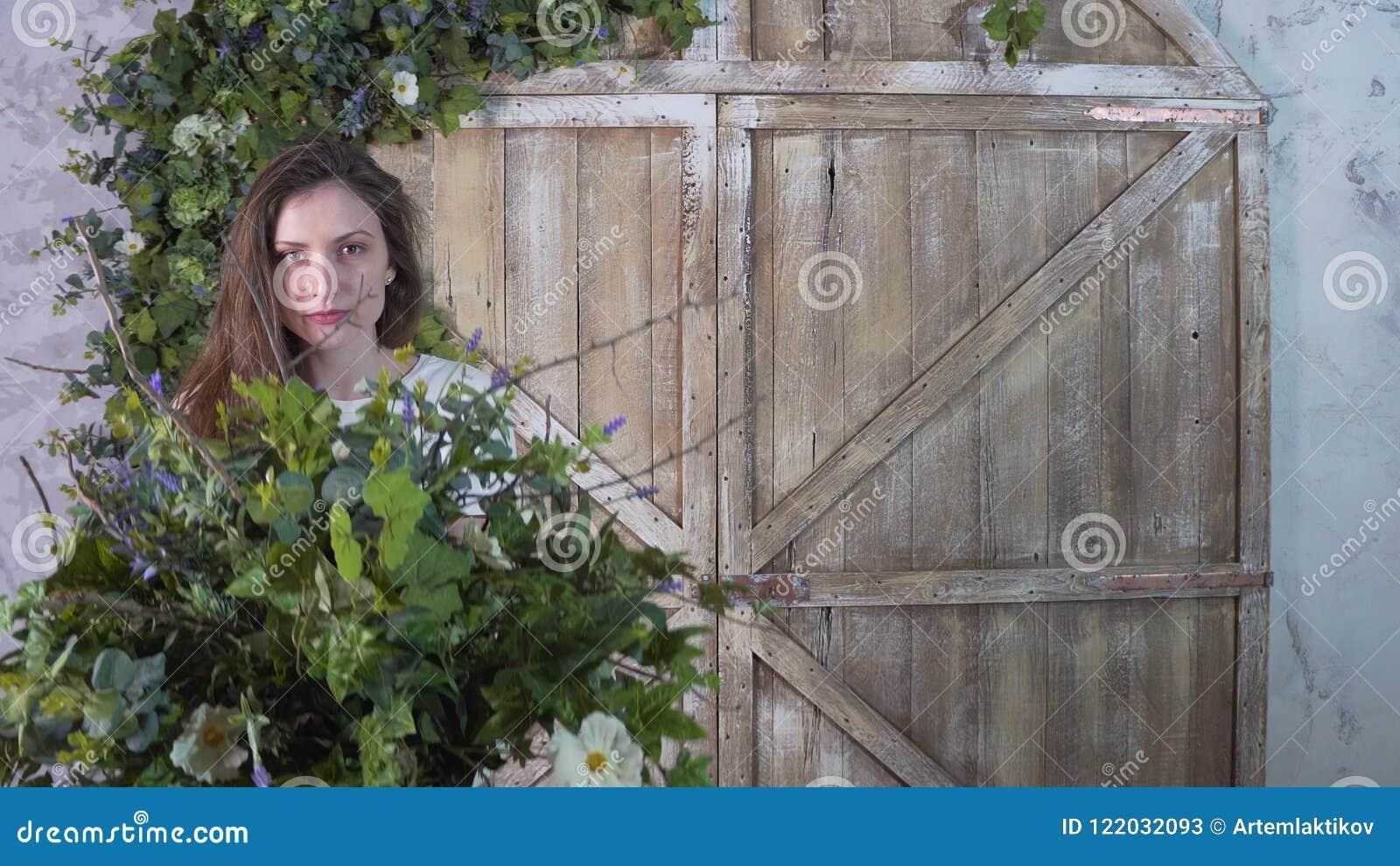 Флорист девушки держит вазу цветков в ее руках, пряча ее сторону