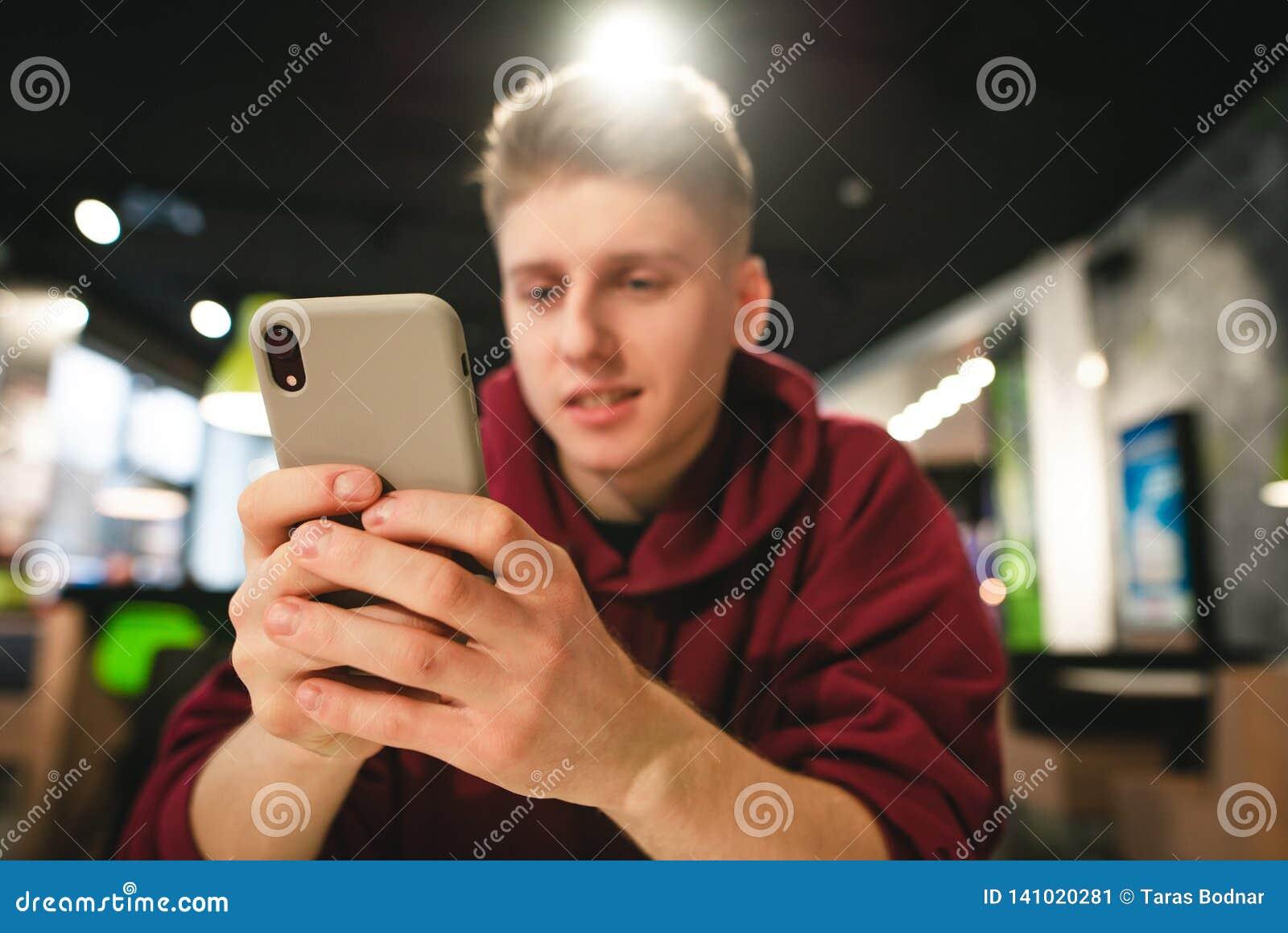 Фокус на смартфоне, положительный парень использует интернет на смартфоне Молодой человек использует смартфон в кафе фаст-фуда