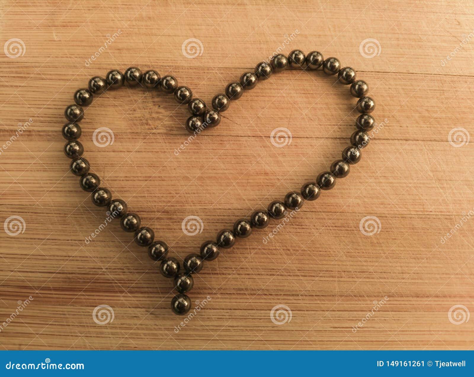 Форма сердца с подшипниками на деревянной предпосылке