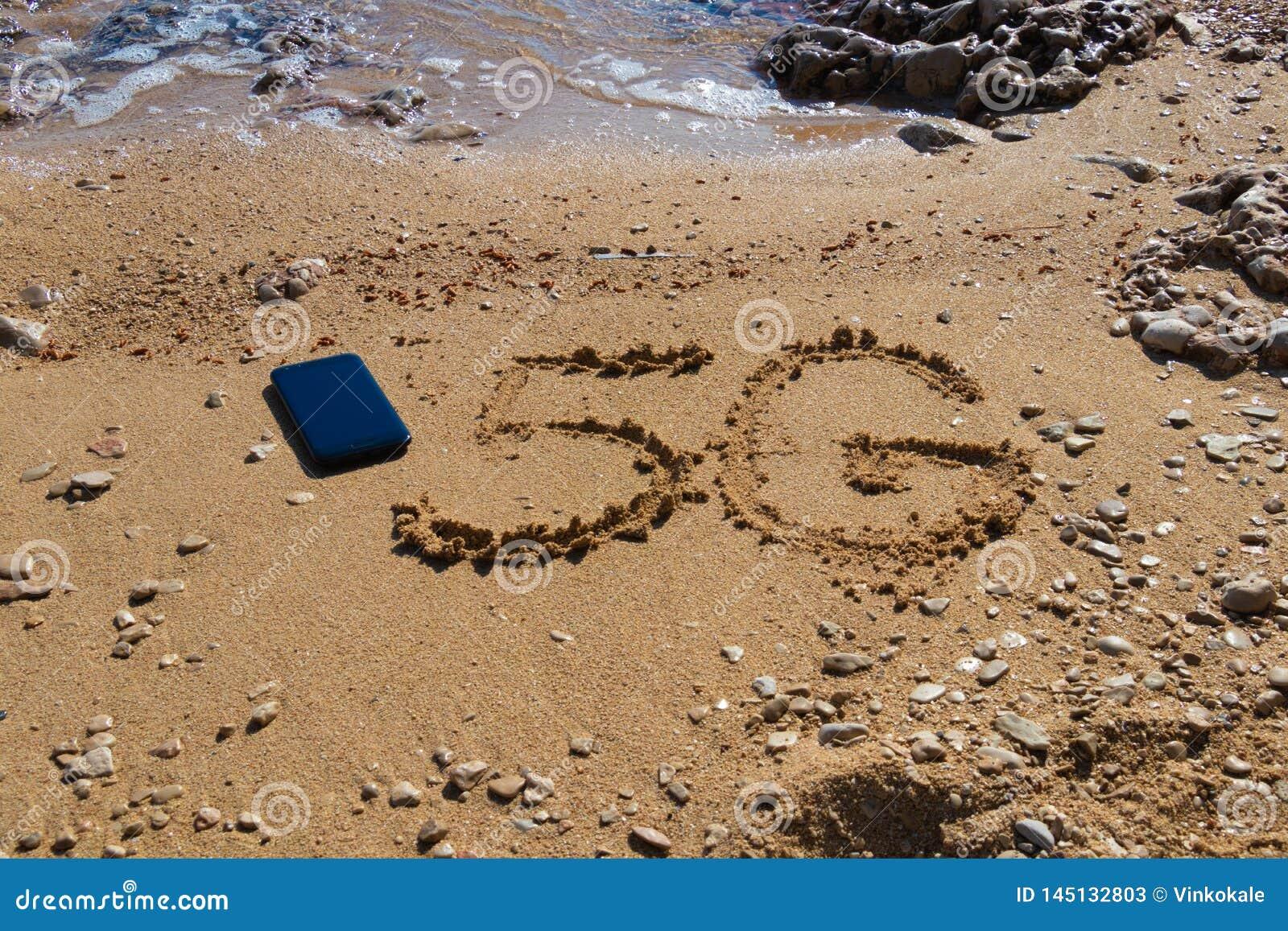 форма 5G на песке около мобильного телефона