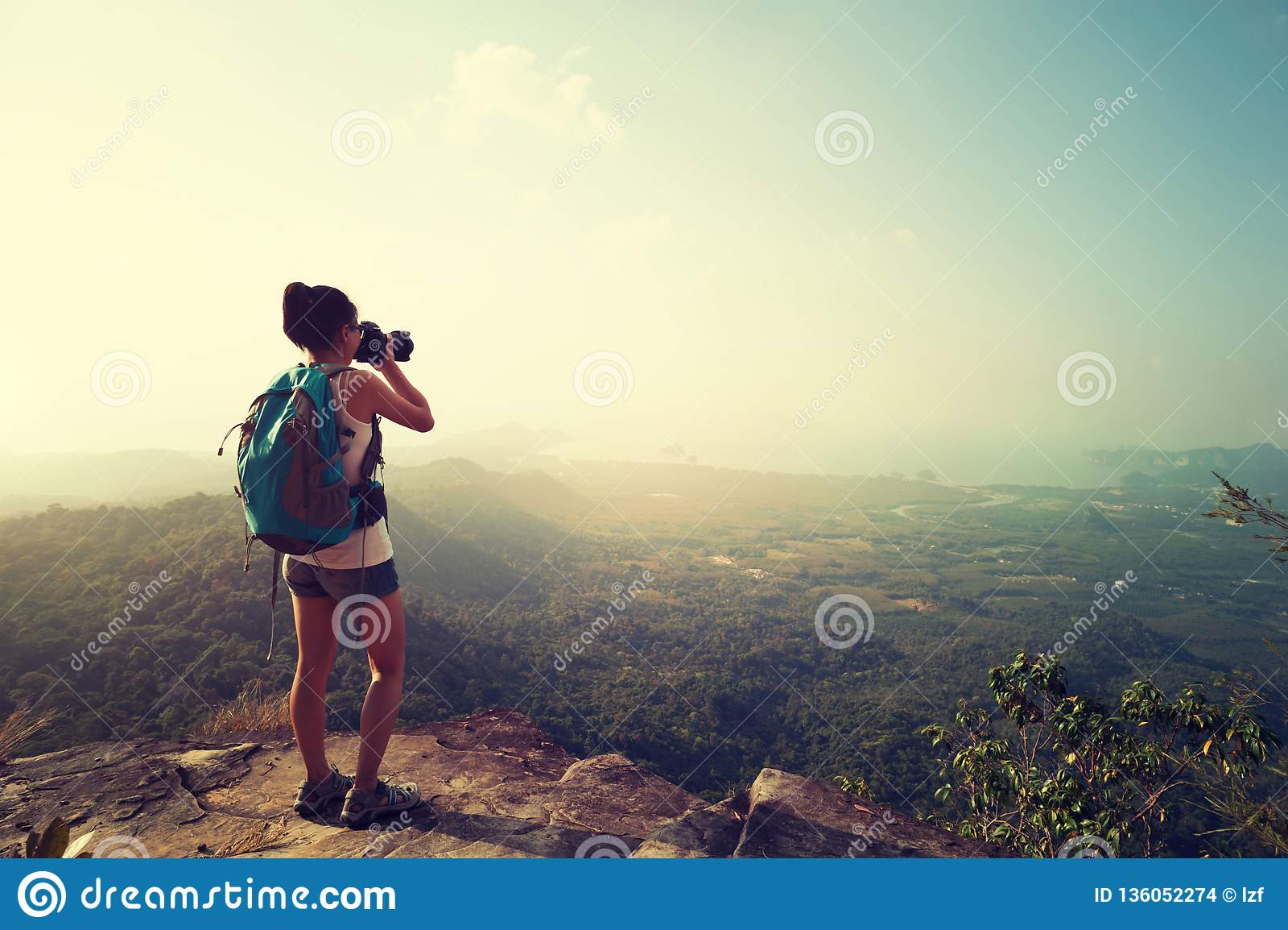 Фотограф женщины принимая фото на горный пик