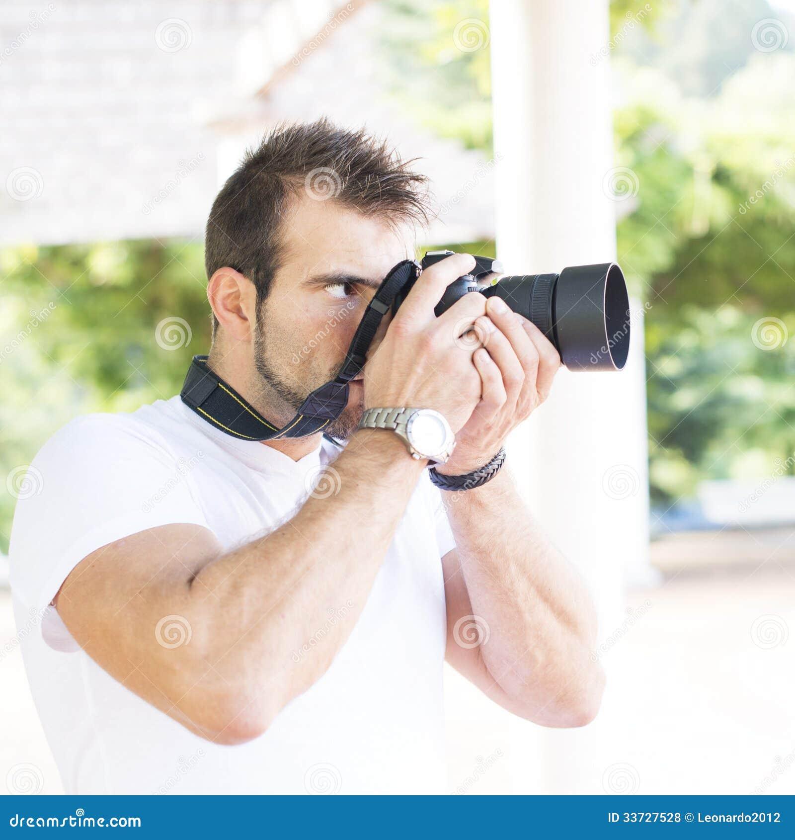 Фотограф используя профессиональную камеру.