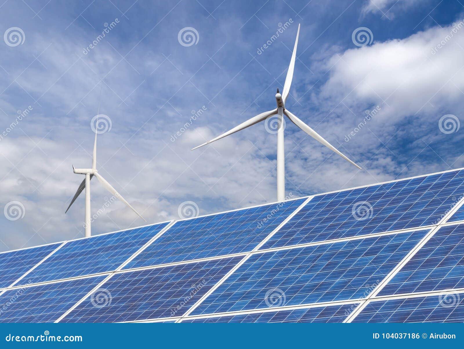 Фотоэлементы при ветротурбины производя электричество в гибридной станции систем электростанции на предпосылке голубого неба