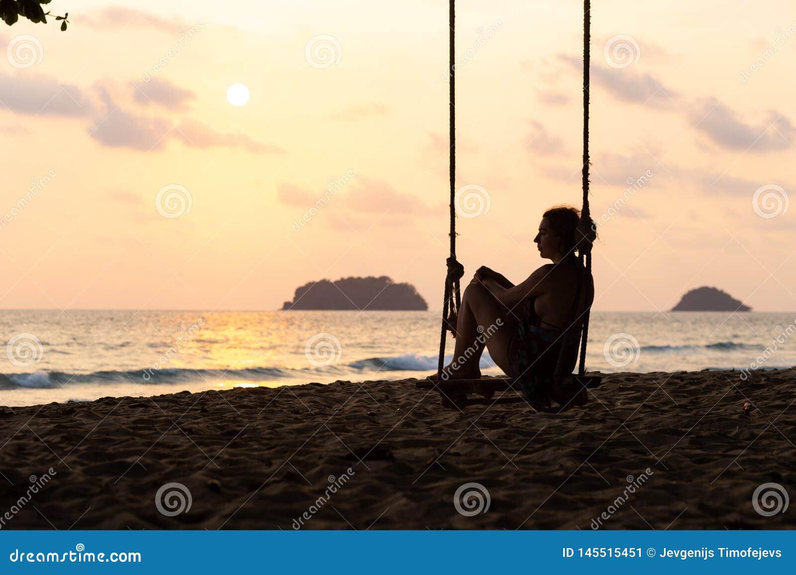 Фото блога перемещения: Силуэт женщины в платье во время захода солнца с взглядом над морем с небольшим isand на горизонте