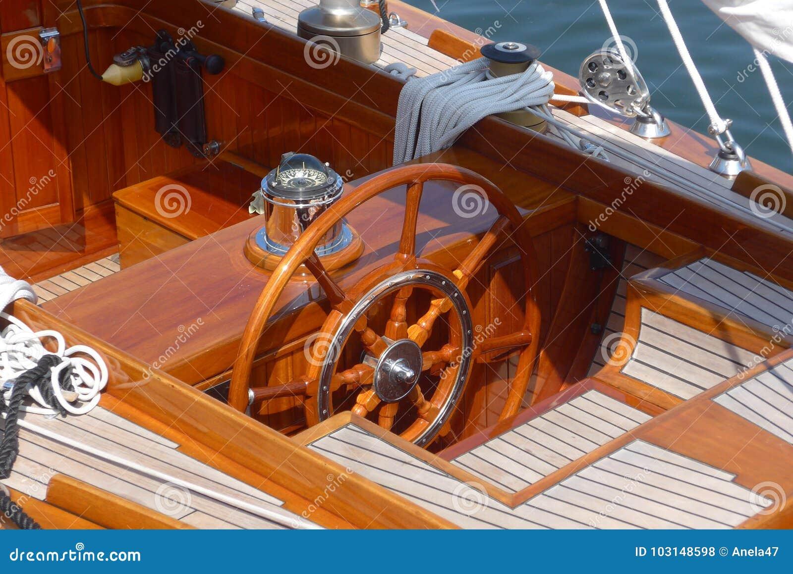 Фото детали плавания плавать, рулевое колесо, палуба teak и компас