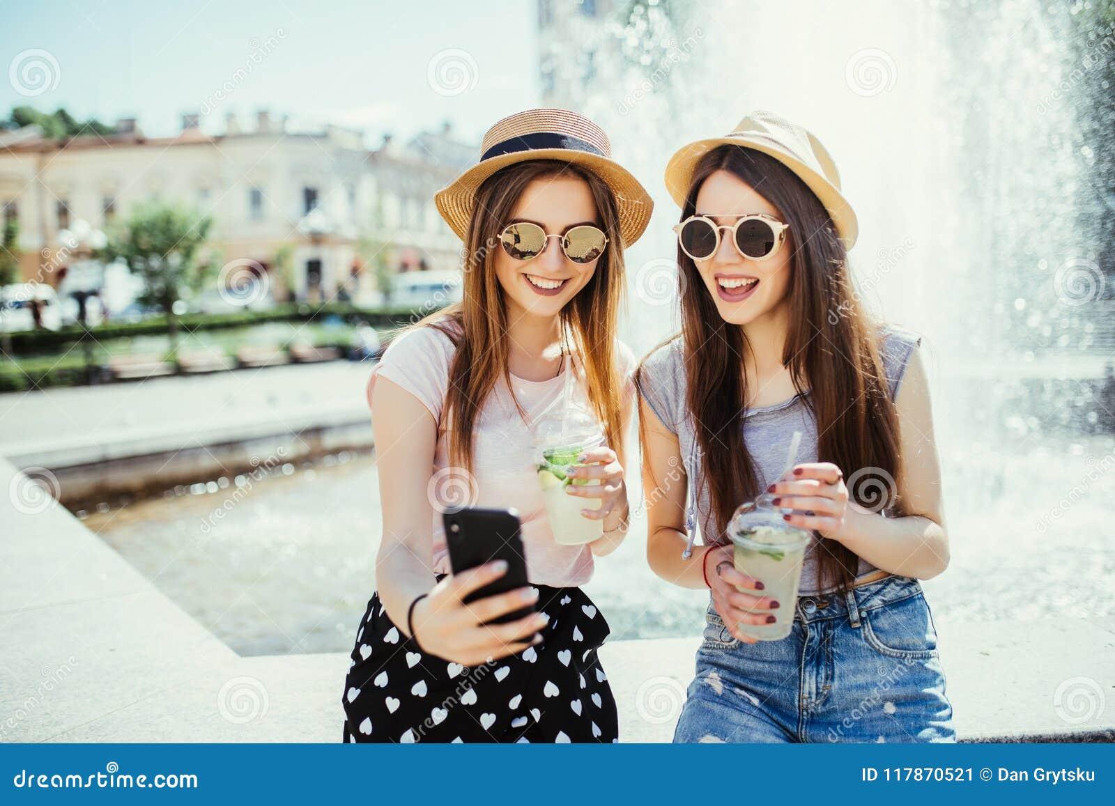 Фото довольных 2 женщин смешанной гонки получает хорошие новости на мобильном телефоне, получает электронную почту или сделать se