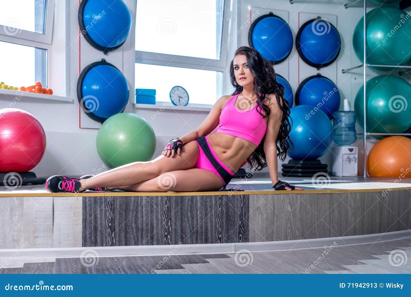 Фото красивой атлетической женщины представляя в спортзале