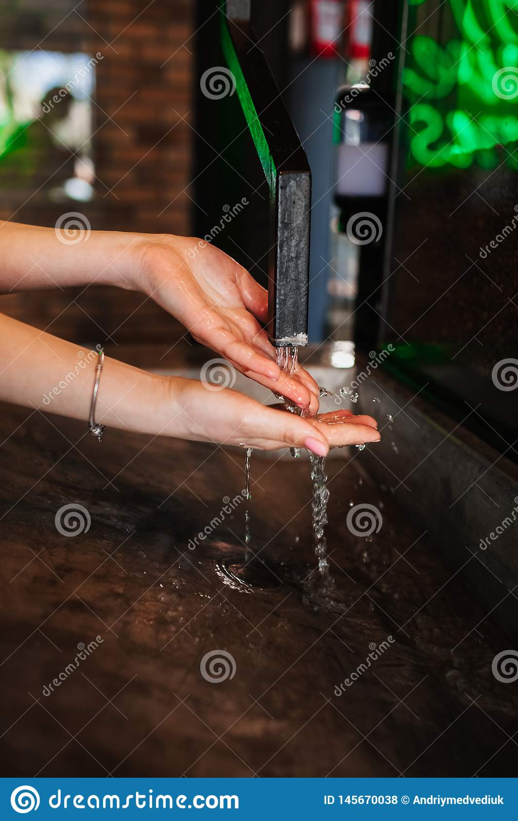 Фото крупного плана рук женщины моя в кафе подачи воды в руки вода от труб