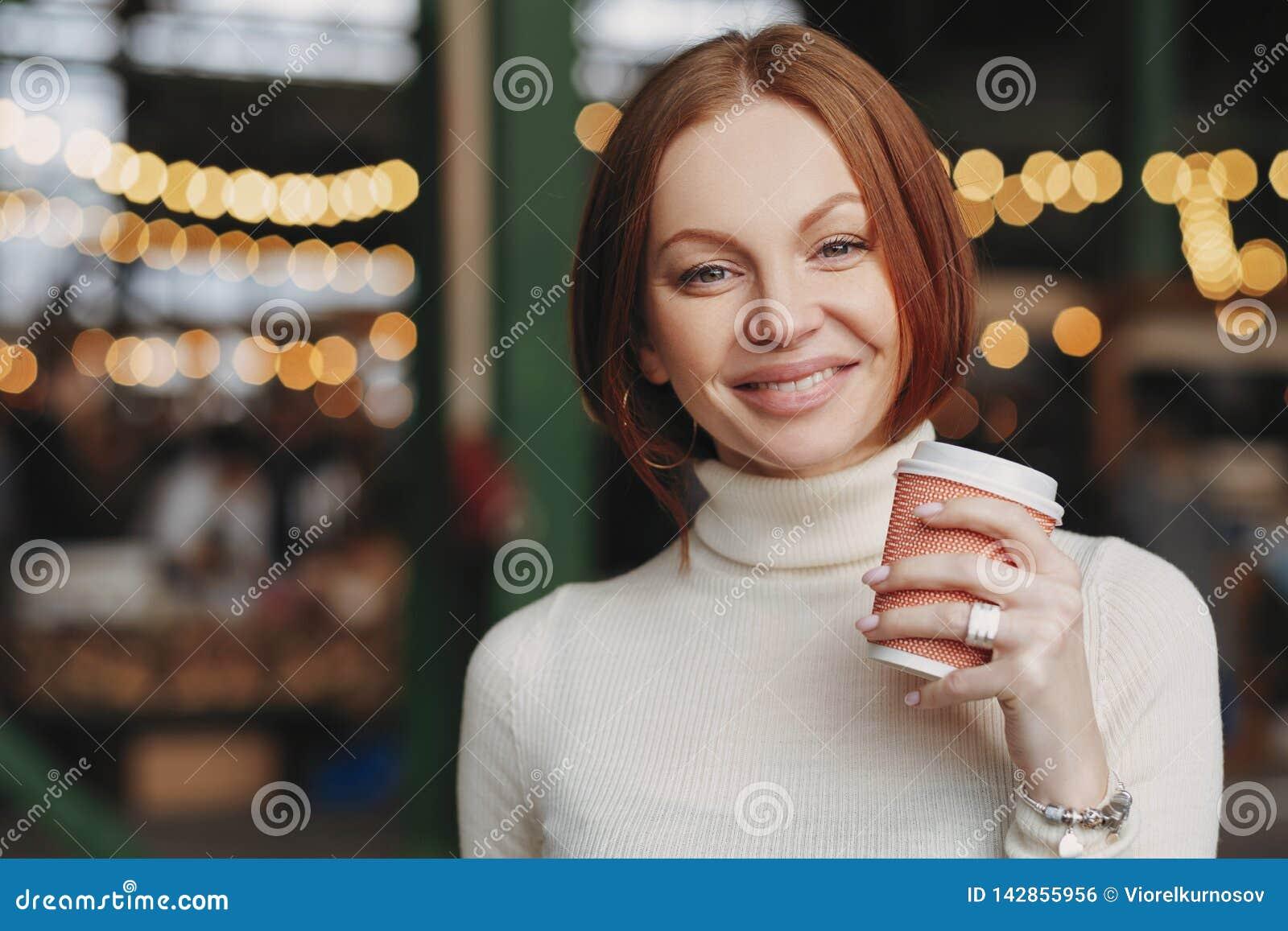 Фото привлекательной молодой женщины держит на вынос кофе, угождало выражению, зубастой улыбке, одетой в белом прыгуне, представл
